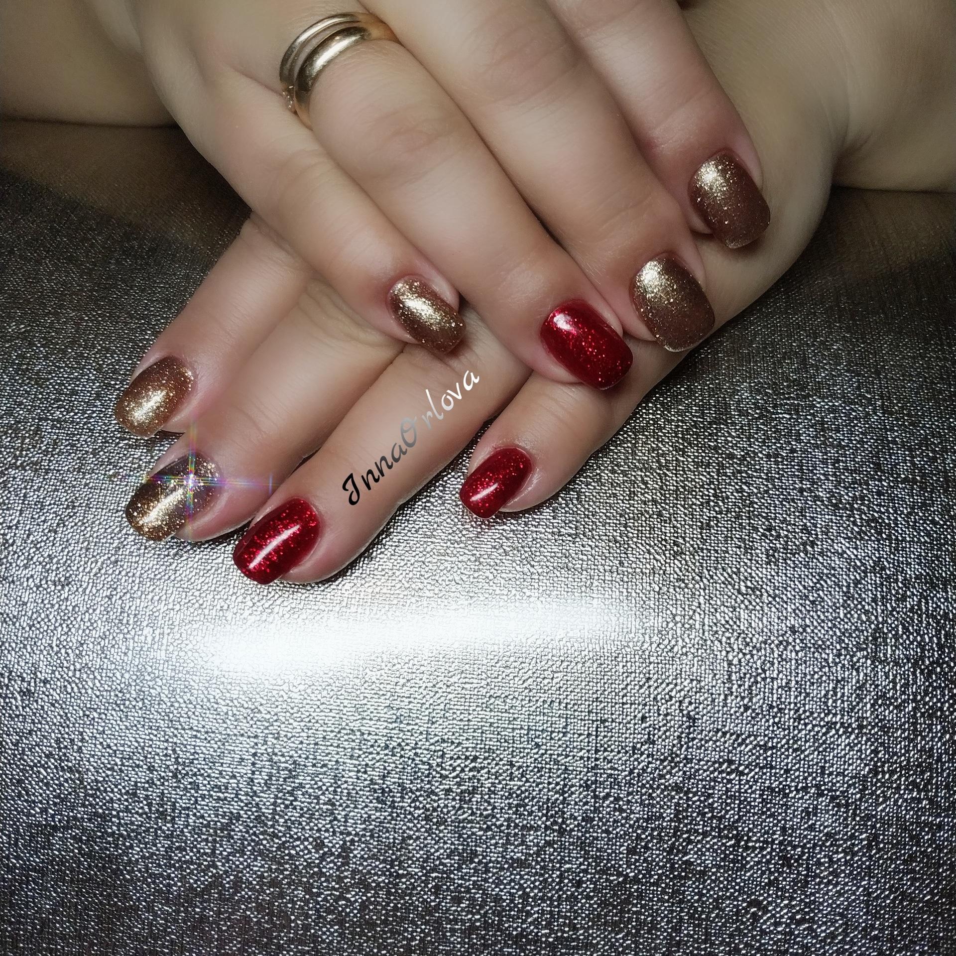 Блестящий золотой маникюр с тёмно-красным дизайном.