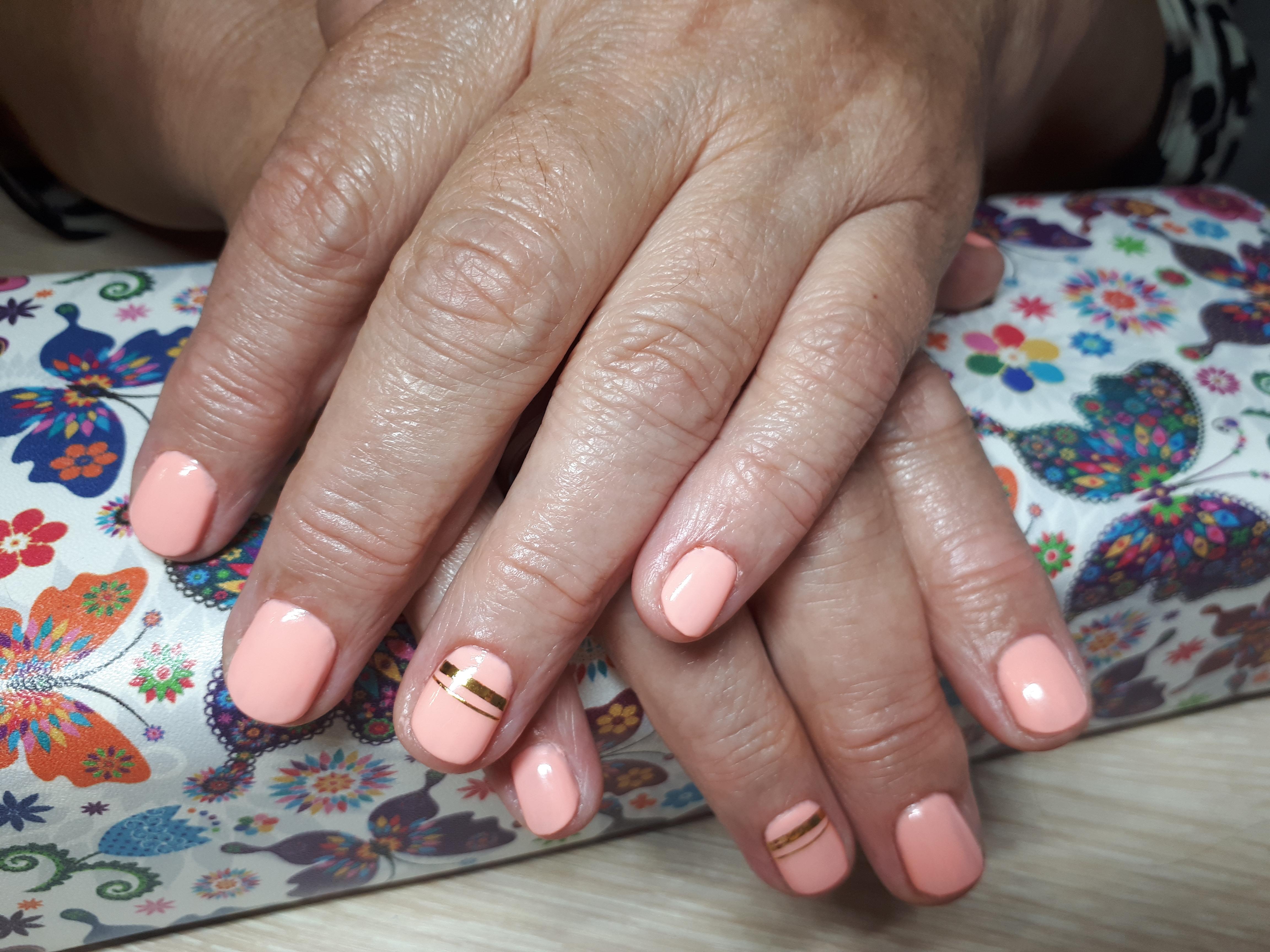 Маникюр с золотыми полосками в персиковом цвете на короткие ногти.