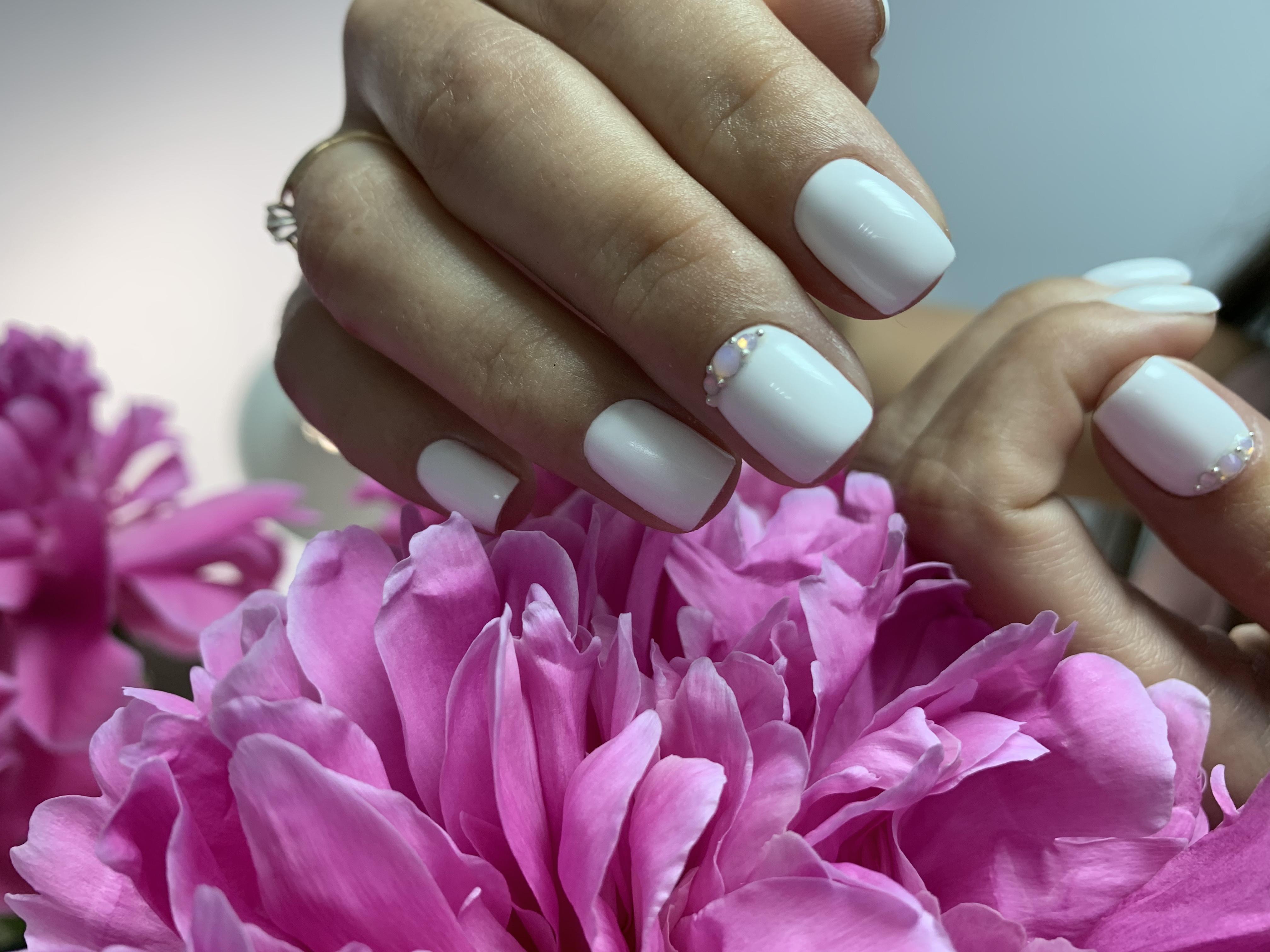 Маникюр со стразами в белом цвете на короткие ногти.