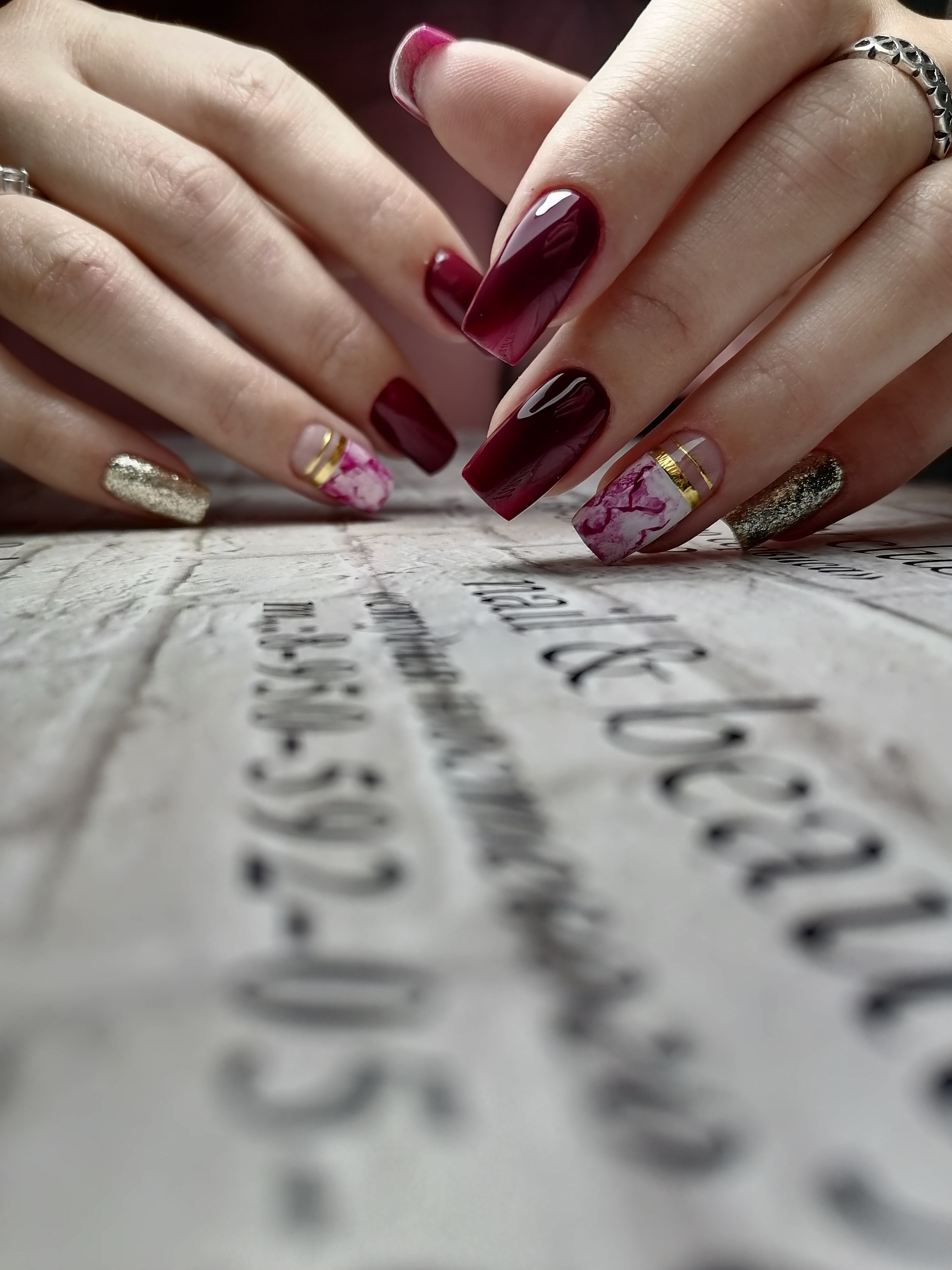 Маникюр с мраморным дизайном, золотыми блестками и полосками в баклажановом цвете на длинные ногти.