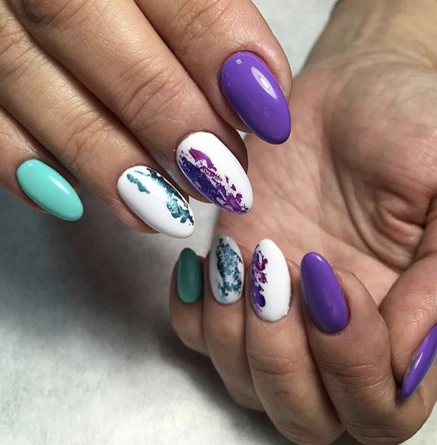 Разноцветный маникюр с белым дизайном, бирюзовой и фиолетовой фольгой.