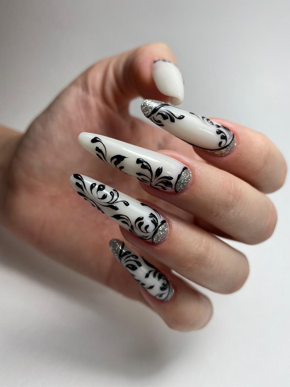 Лунный маникюр с вензелями в белом цвете на длинные ногти.