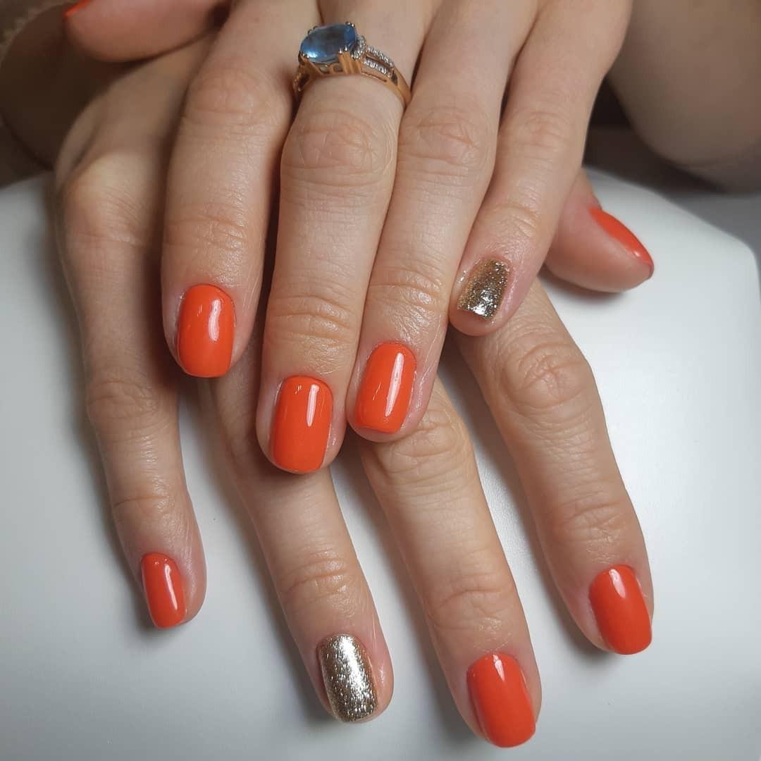 Маникюр с золотыми блестками в оранжевом цвете на короткие ногти.