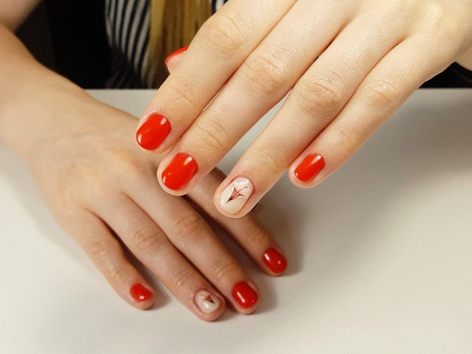 Маникюр с цветочным слайдерами в красном цвете на короткие ногти.