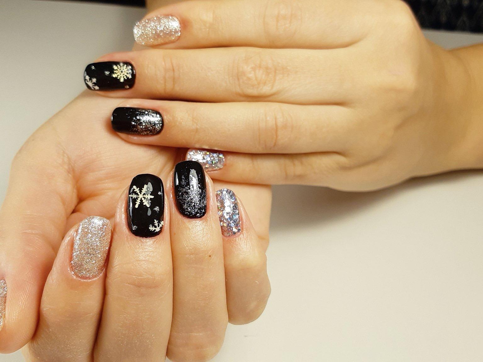 Зимний маникюр со снежинками и серебряными блестками в черном цвете на короткие ногти.