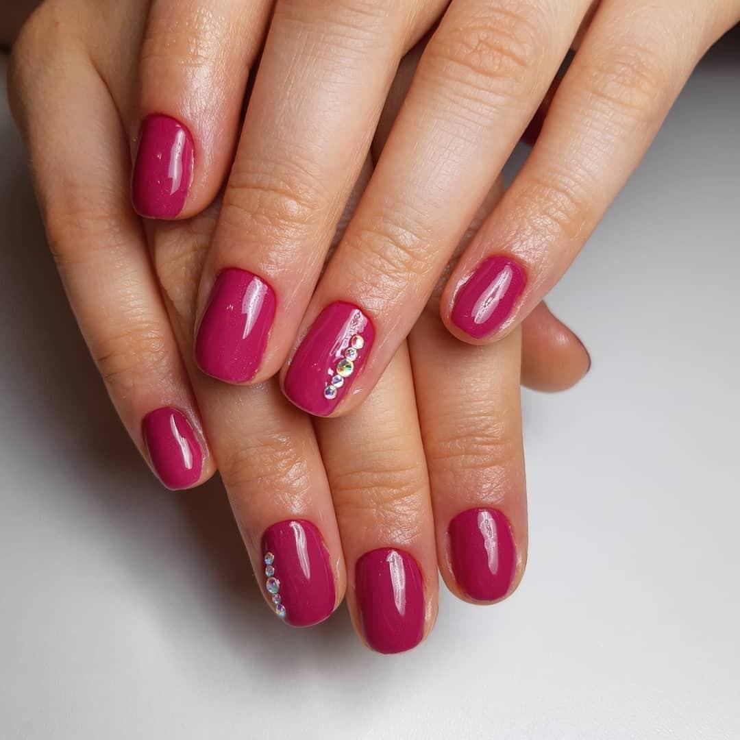Маникюр со стразами в баклажановом цвете на короткие ногти.