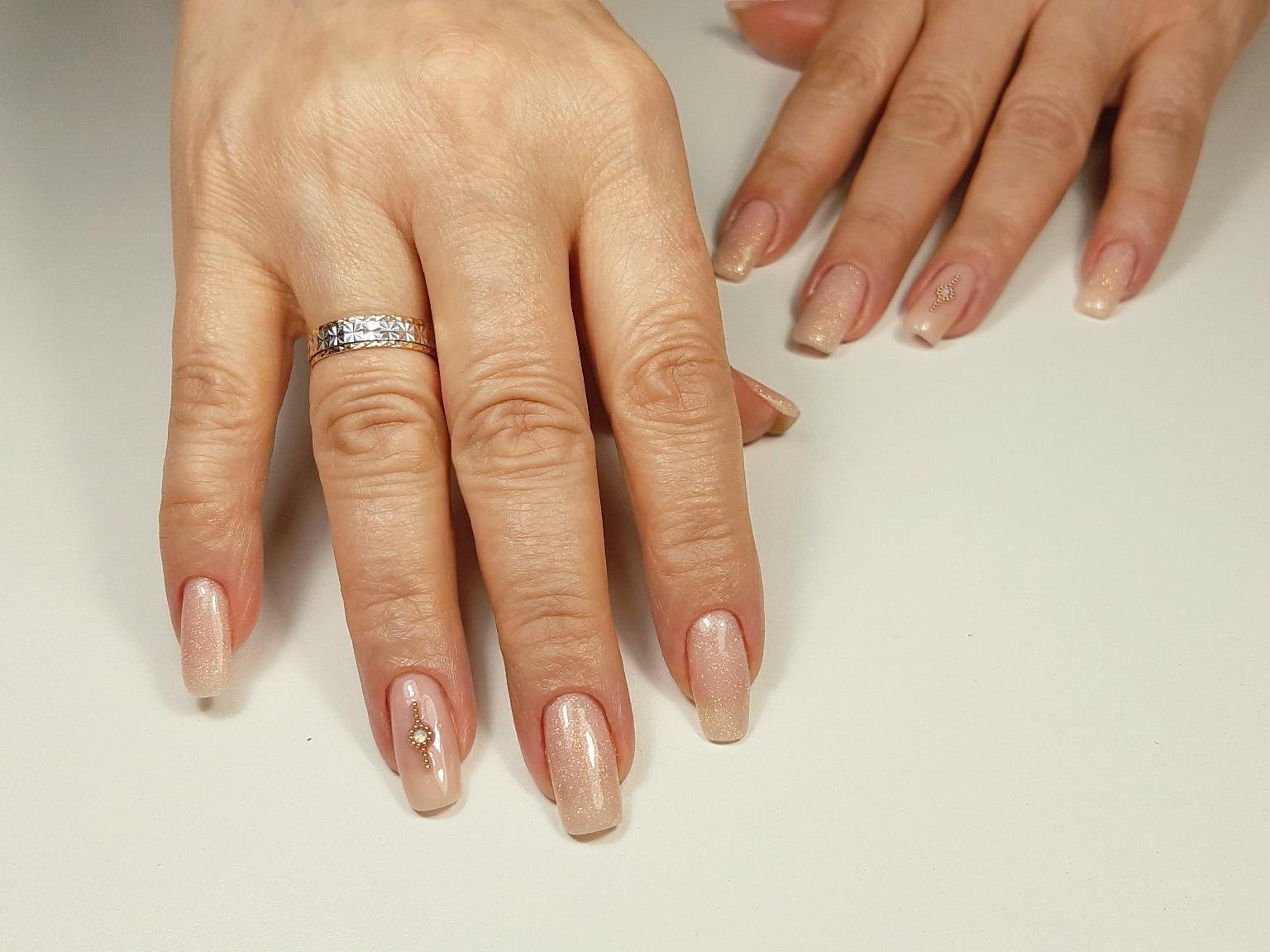Нюдовый маникюр с блестками и стразами на длинные ногти.
