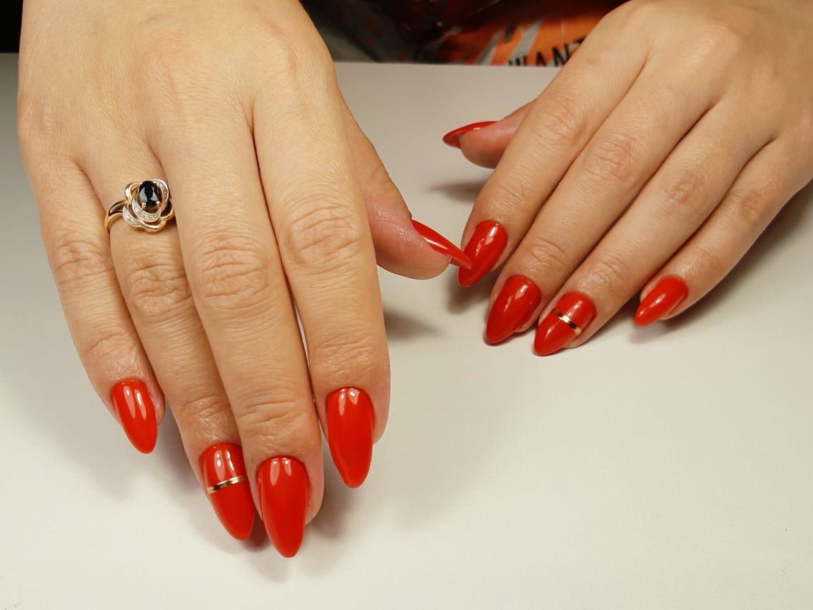 Маникюр с золотыми полосками в красном цвете на длинные ногти.