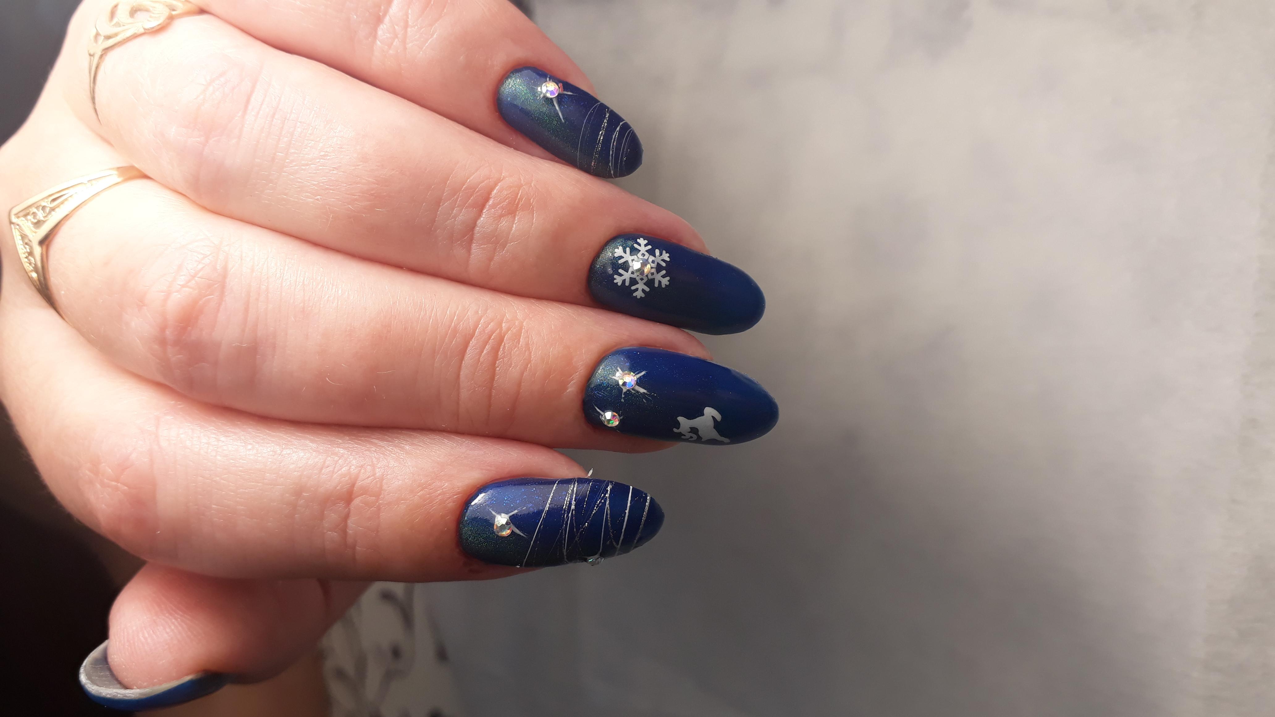 Маникюр в тёмно-синем цвете с новогодним стемпингом, стразами и паутинкой.