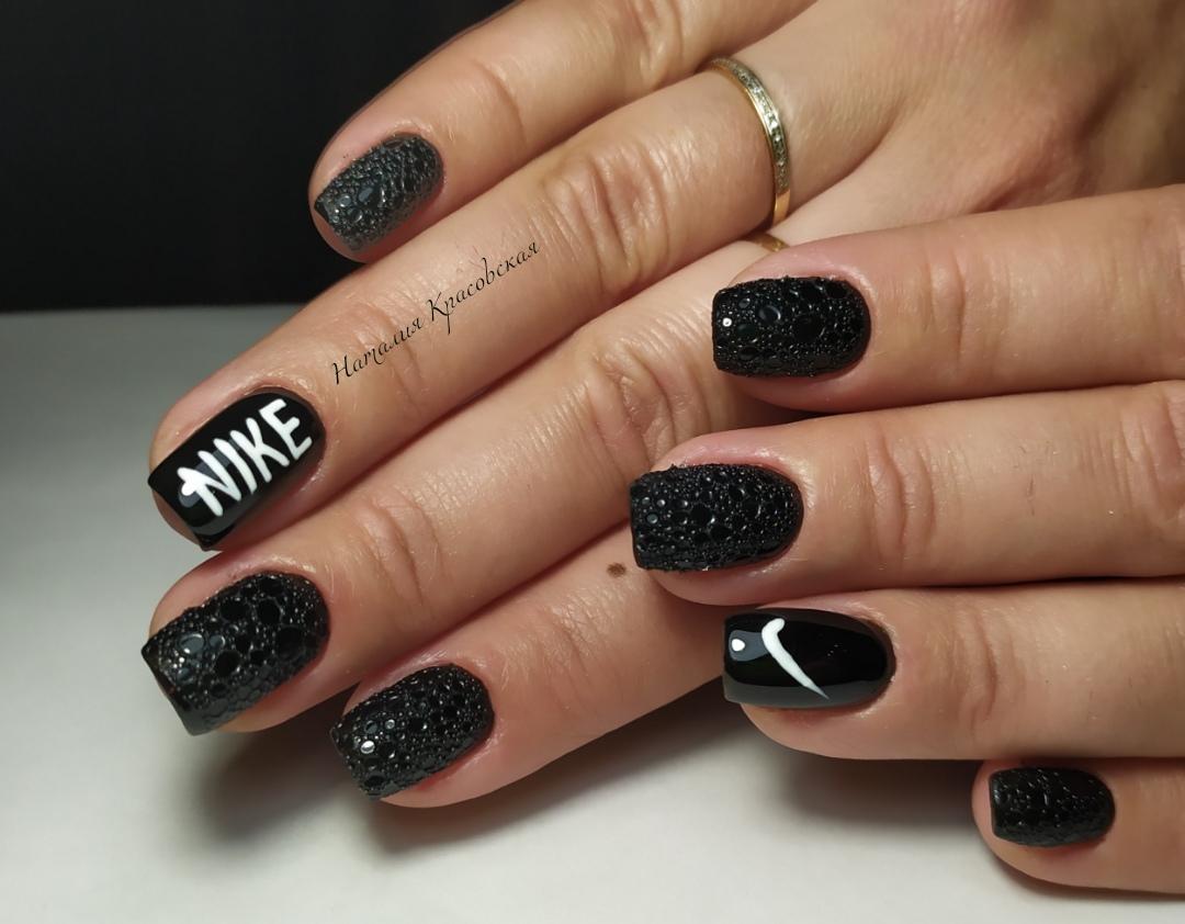 Маникюр с bubble-эффектом и надписями в черном цвете на короткие ногти.