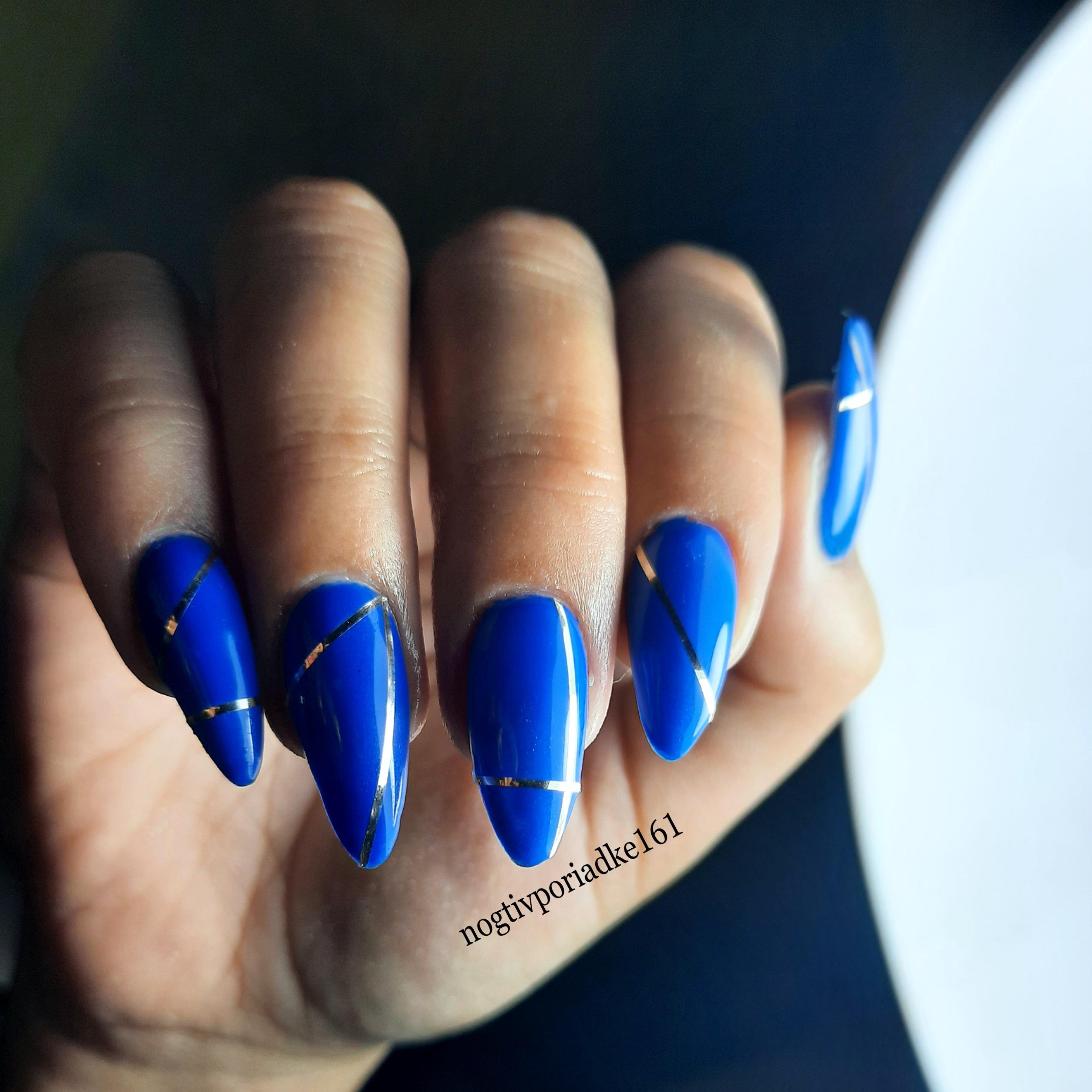 Маникюр с серебряными полосками в синем цвете на длинные ногти.