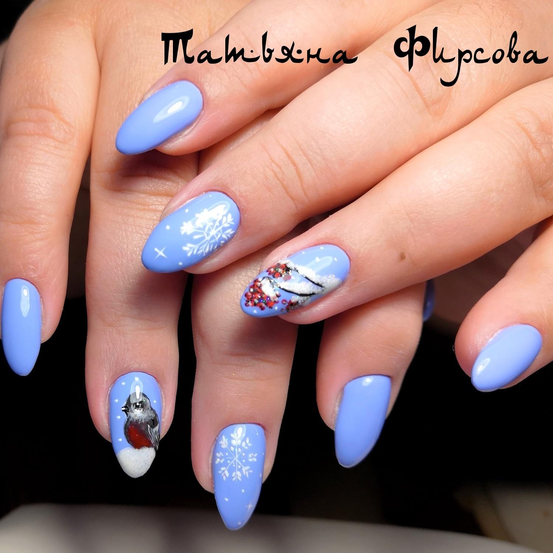 Зимний маникюр со снегирем и снежинками в голубом цвете.