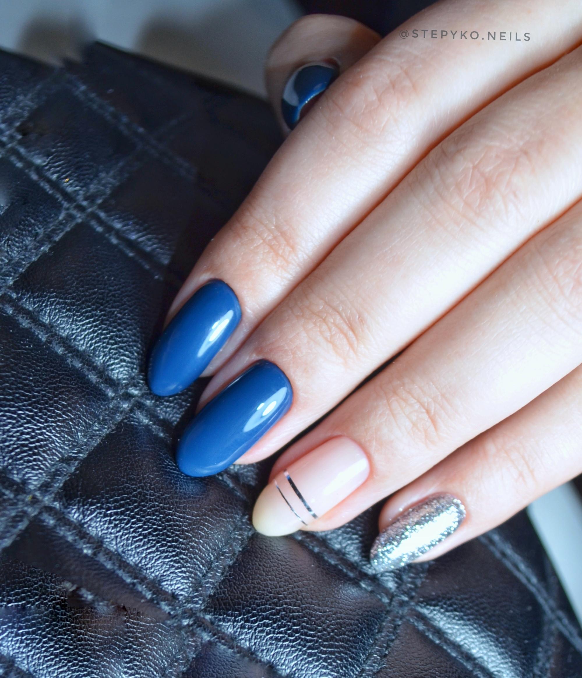 Маникюр с серебряными блестками и полосками в синем цвете.