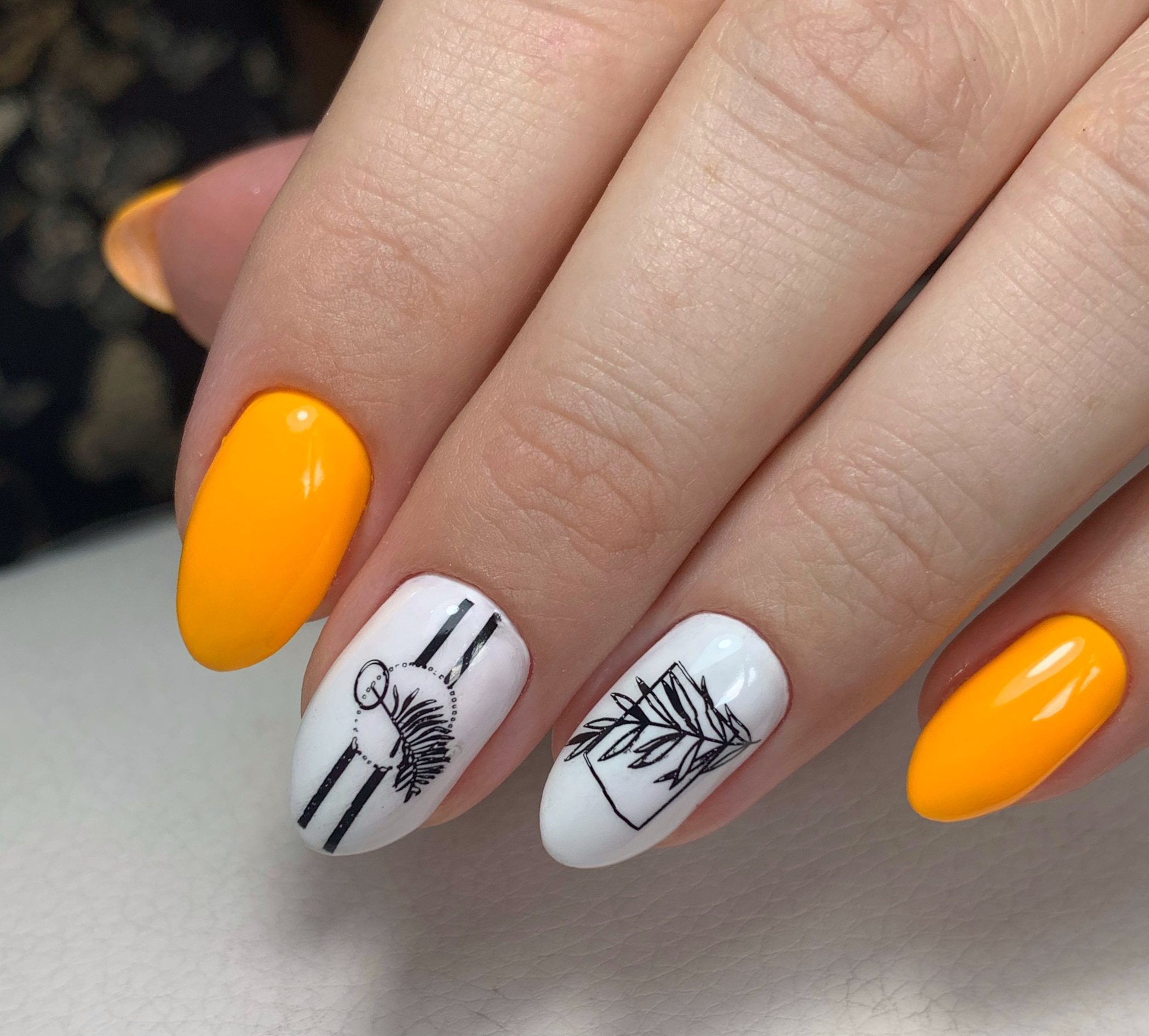 Летний маникюр с растительными слайдерами в оранжевом цвете.