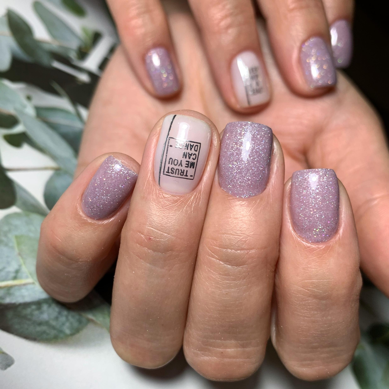 Маникюр с надписями и блестками в сиреневом цвете на короткие ногти.