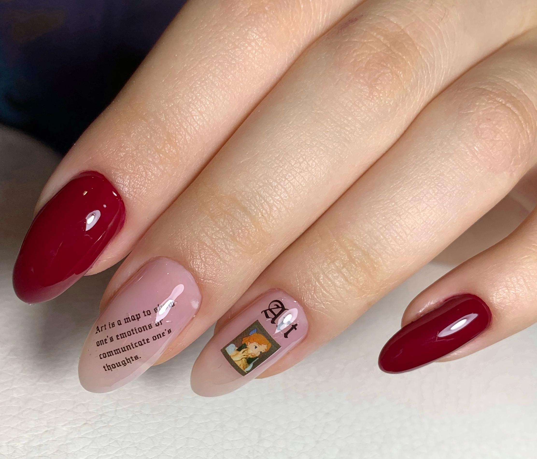 Маникюр со слайдерами и надписями в темно-красном цвете на длинные ногти.