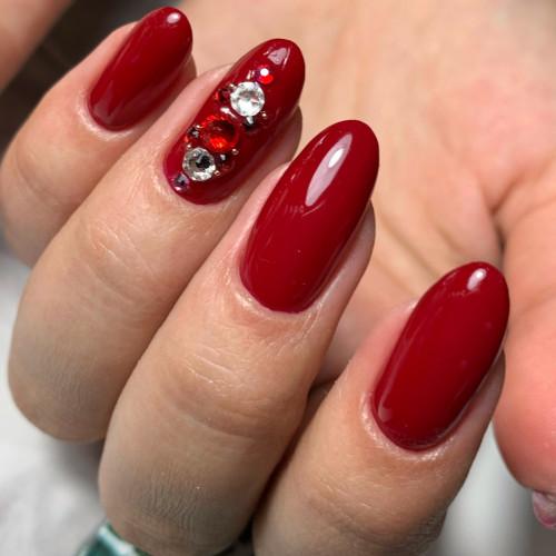 На курсах учат делать маникюр со стразами в темно-красном цвете на длинные ногти.