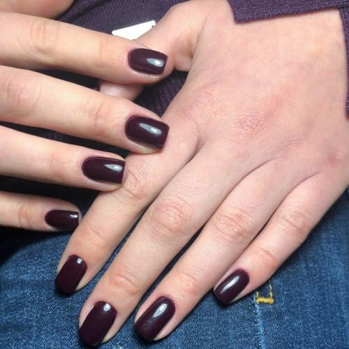 Темный лак на коротких ногтях.