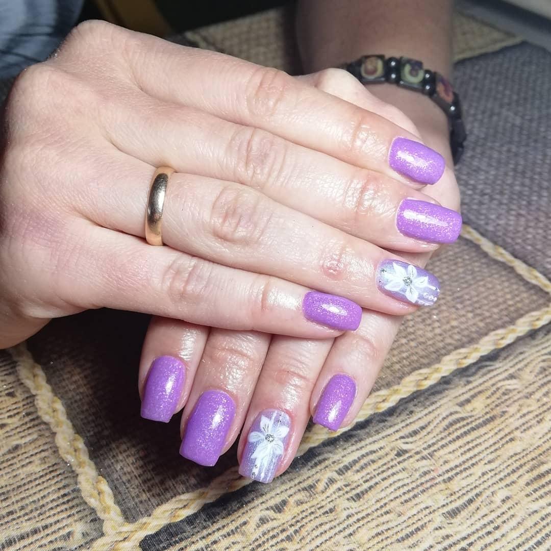 Маникюр с цветочным рисунком и блестками в фиолетовом цвете на короткие ногти.