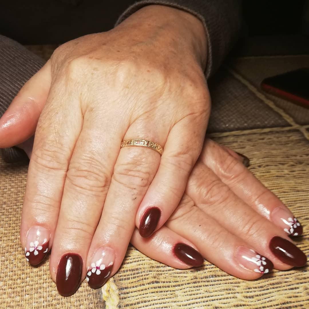 Маникюр с цветочным рисунком в темно-красном цвете на короткие ногти.