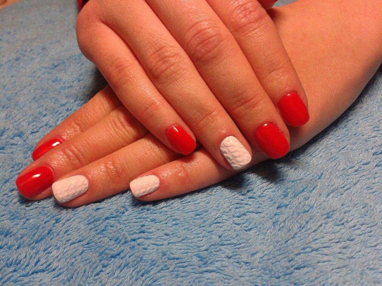 Маникюр в красном цвете с белым вязаным дизайном.