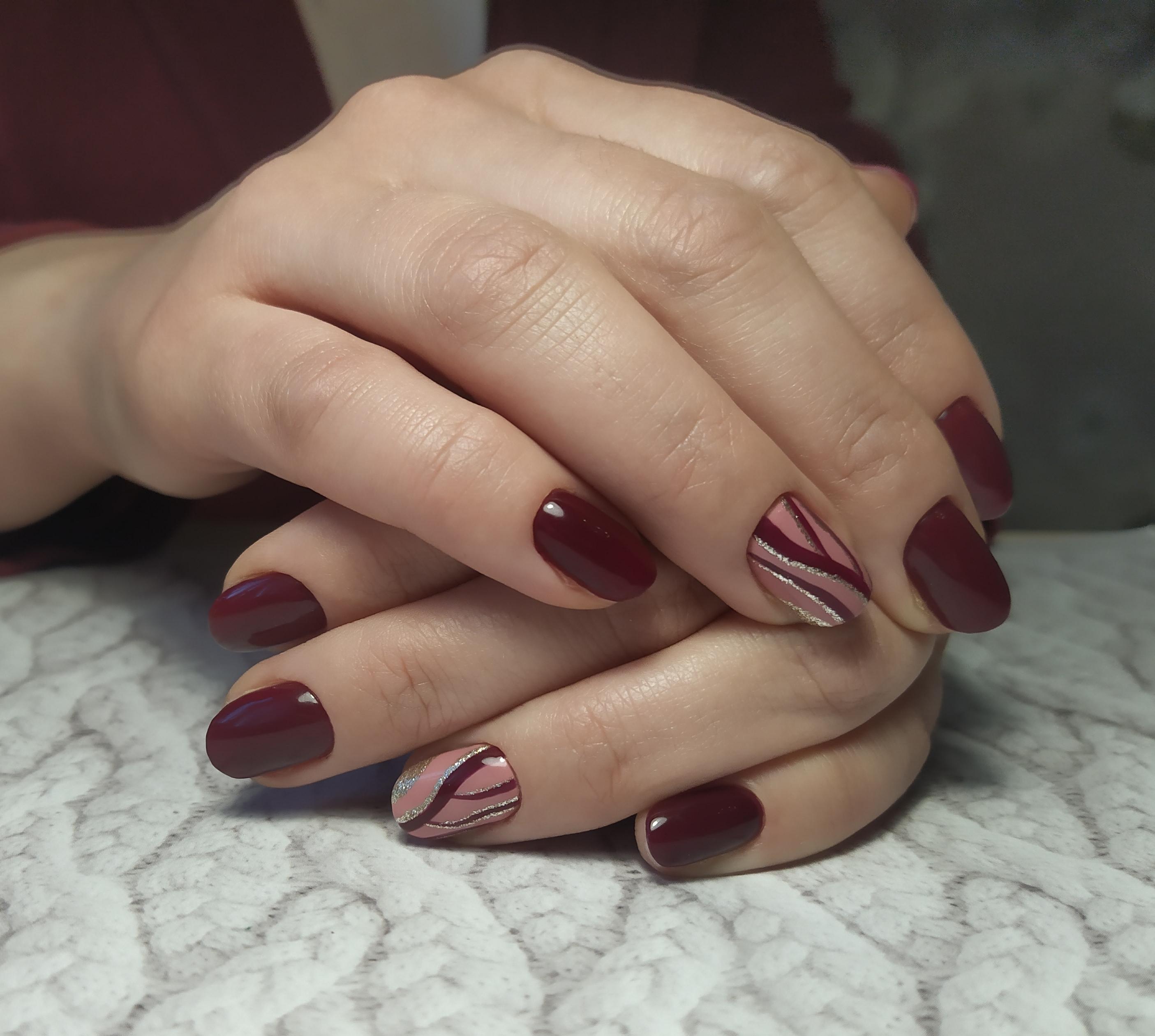 Маникюр с абстрактным рисунком и блестками в темно-красном цвете.