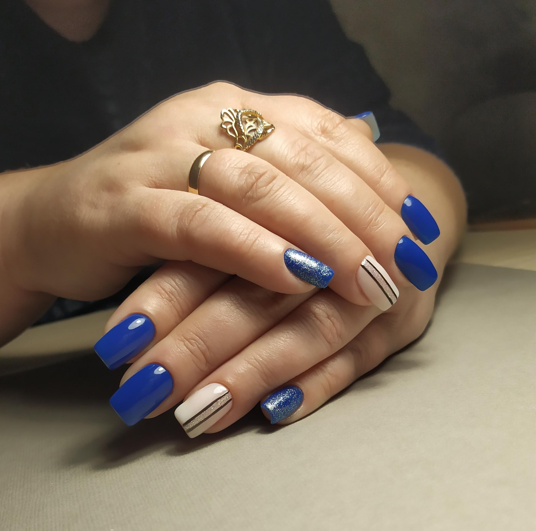 Маникюр с полосками и блестками в синем цвете.