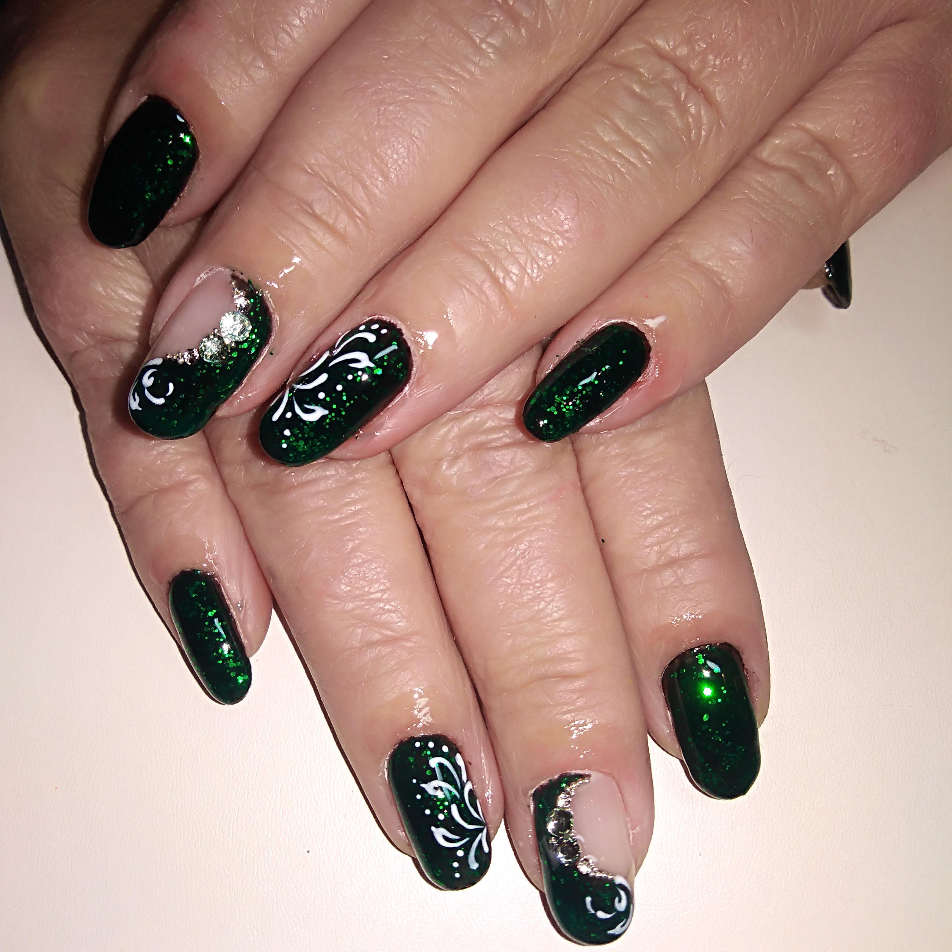 Блестящий маникюр в тёмно-зелёном цвете с вензелями и стразами.