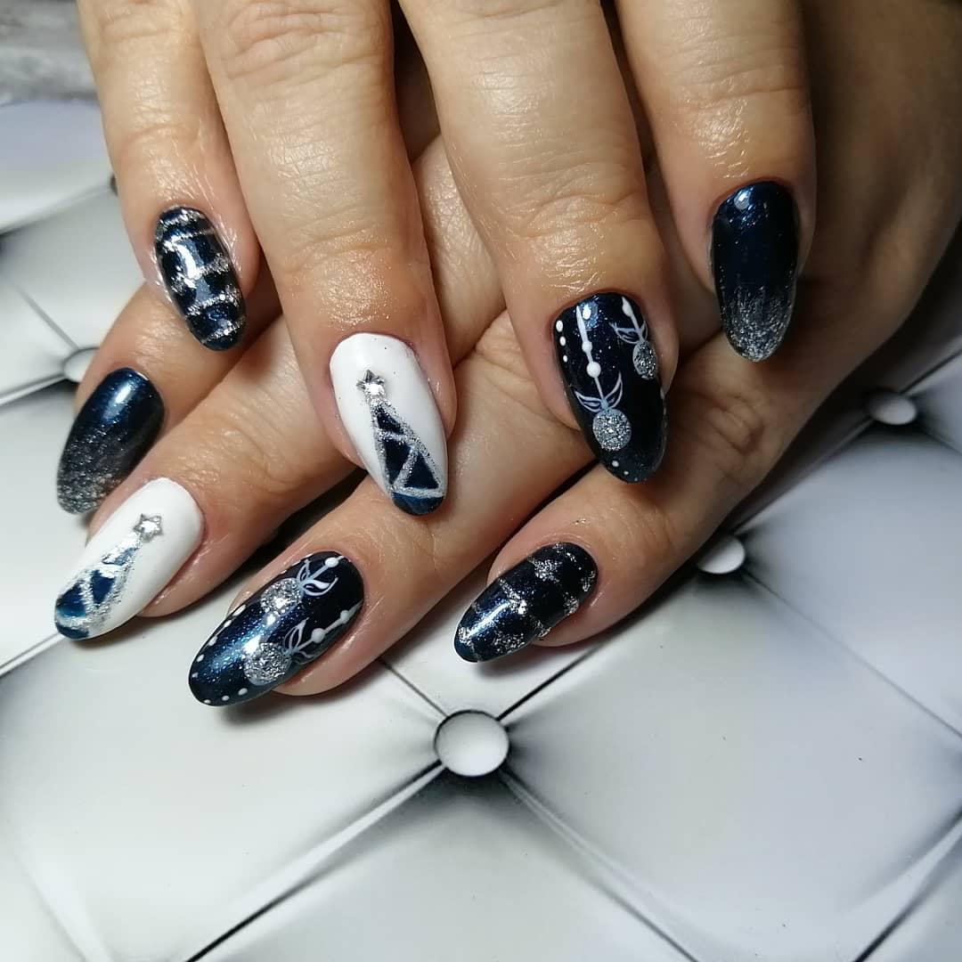 Новогодний маникюр с рисунком и серебряными блестками в темно-синем цвете.