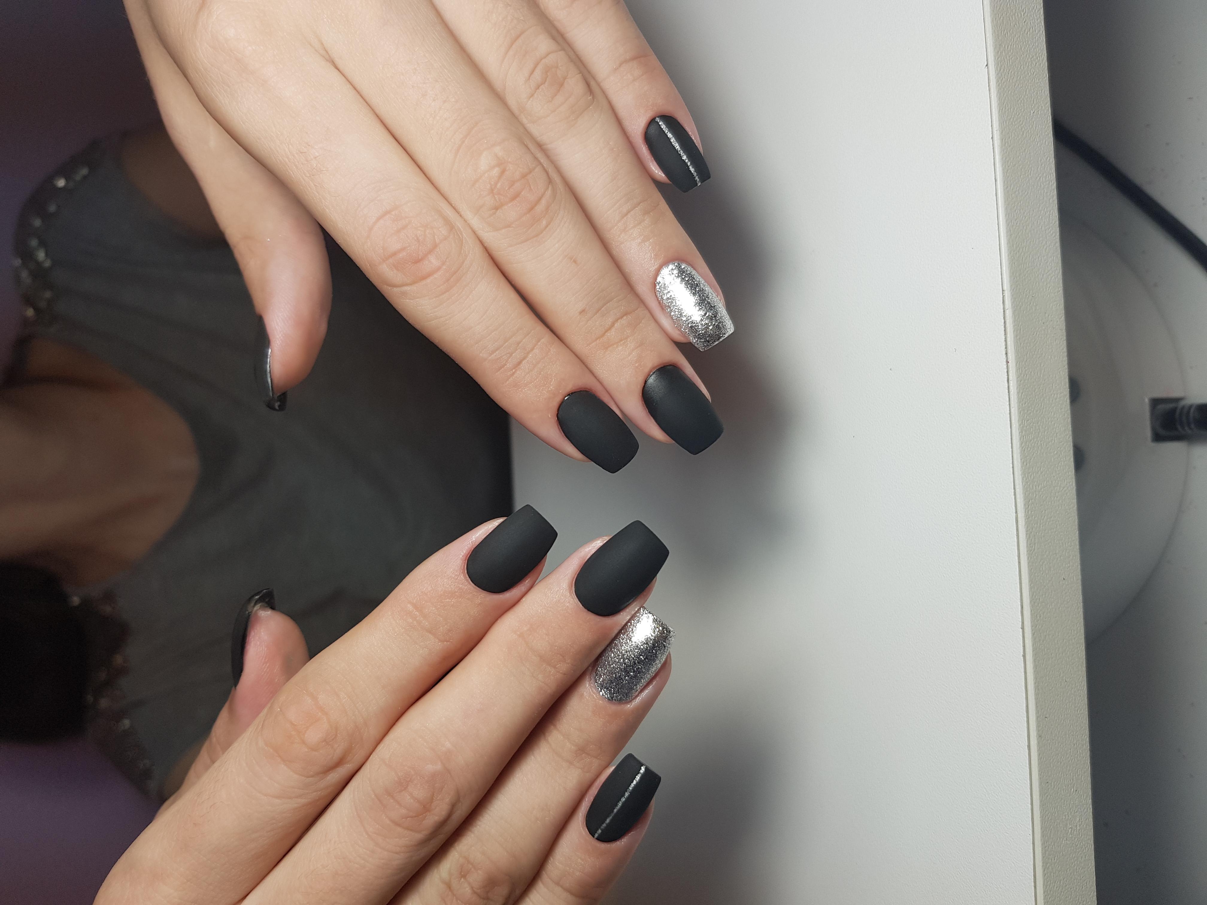 Матовый маникюр с серебряными блестками в черном цвете.