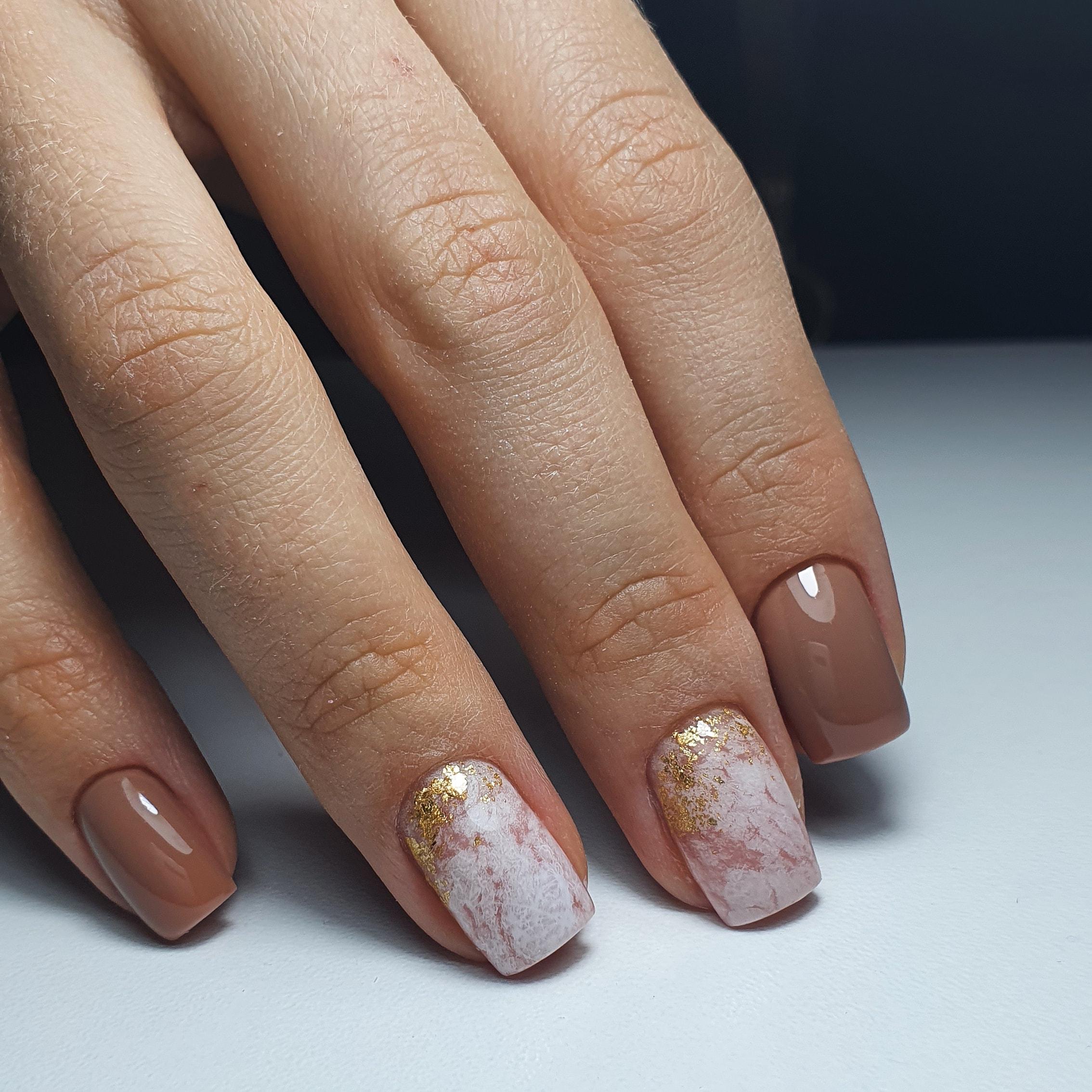 Маникюр с мраморным дизайном и золотой фольгой в коричневом цвете на короткие ногти.