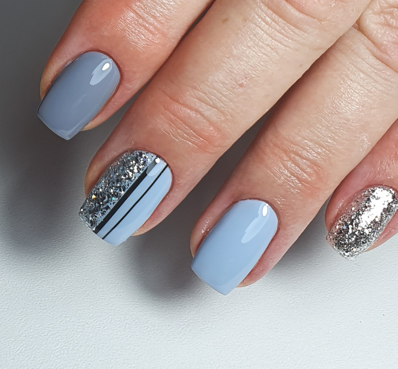 Маникюр с серебряными блестками и полосками в пастельных тонах.