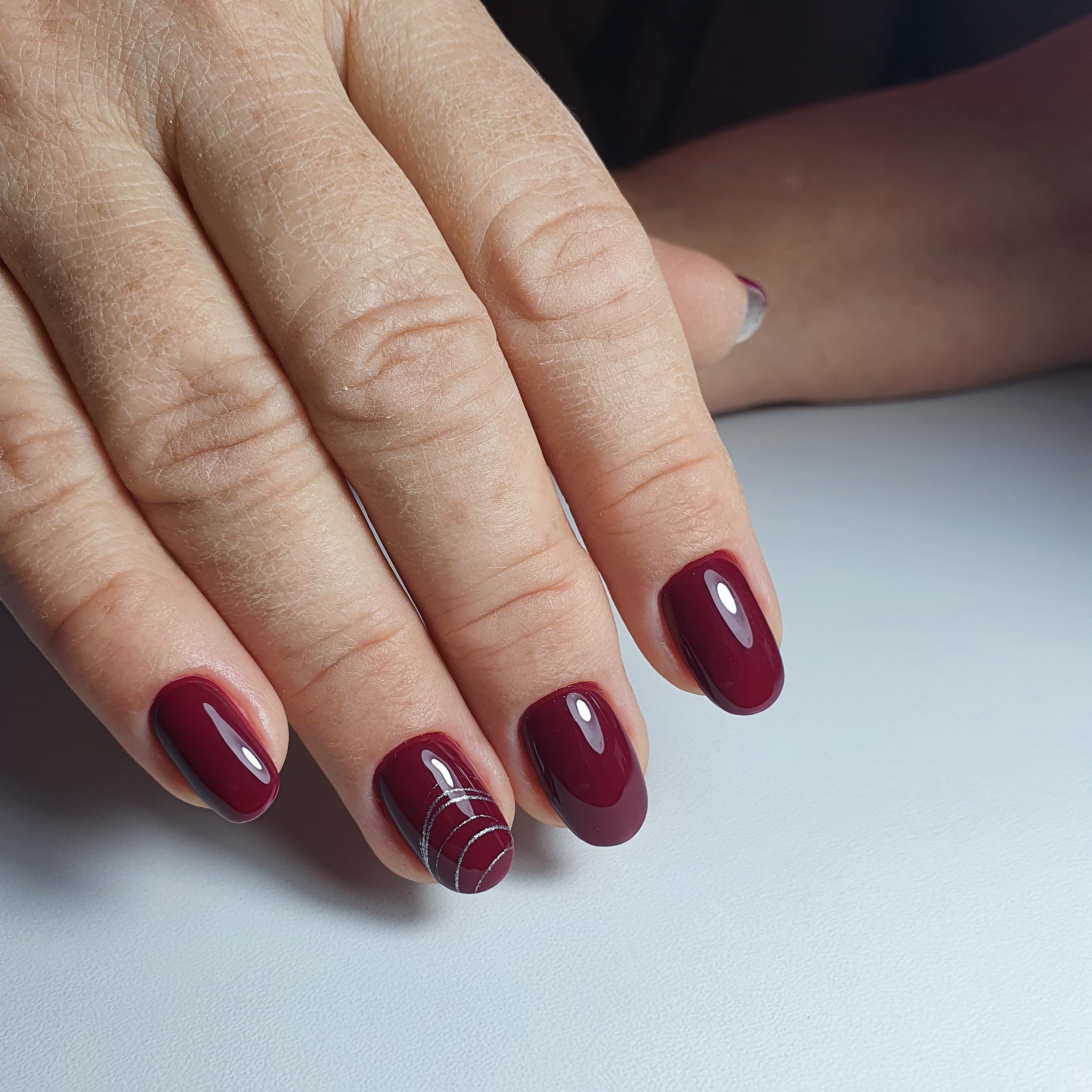 Маникюр с паутинкой в темно-красном цвете на короткие ногти.