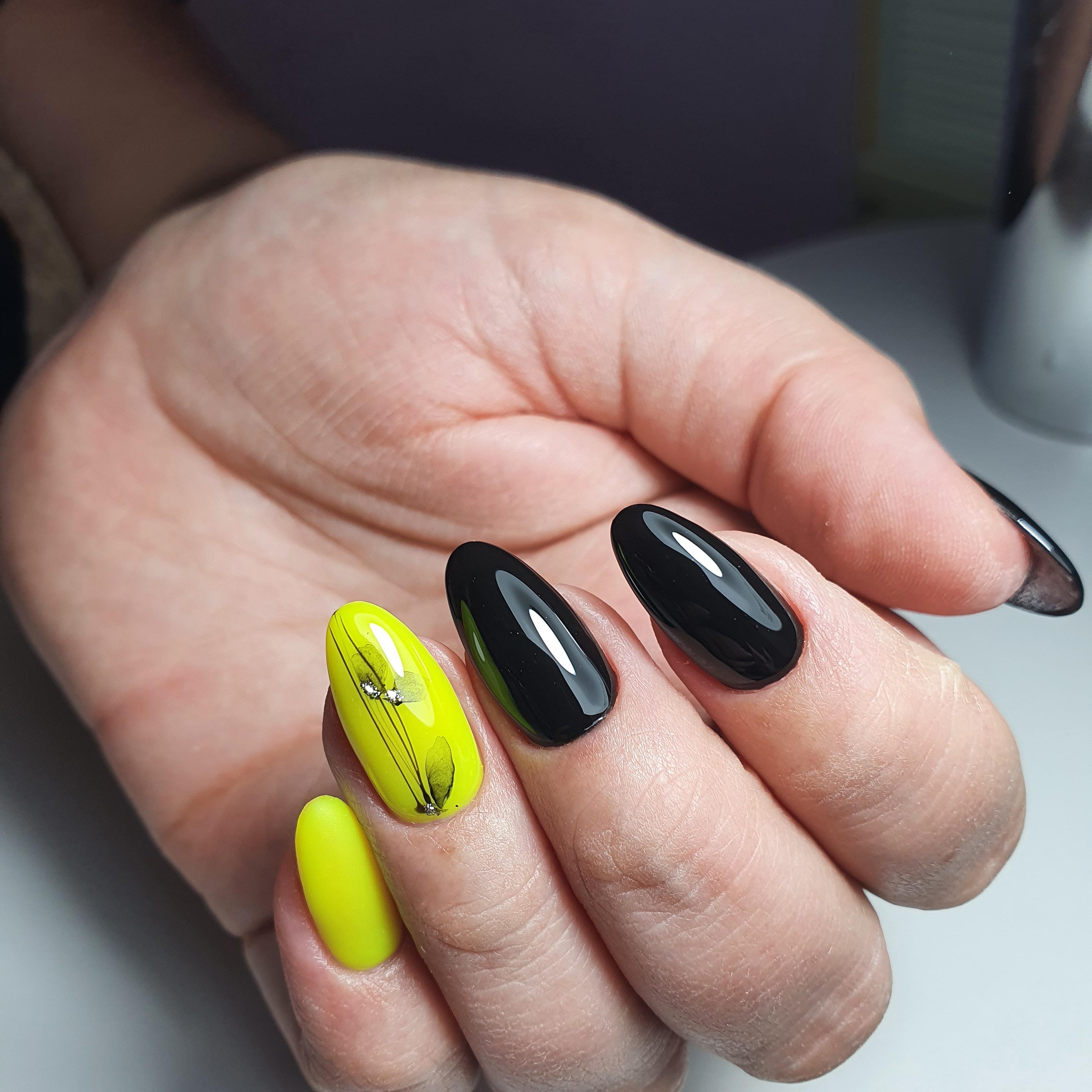 Маникюр с акварельным рисунком и стразами в черном цвете на длинные ногти.