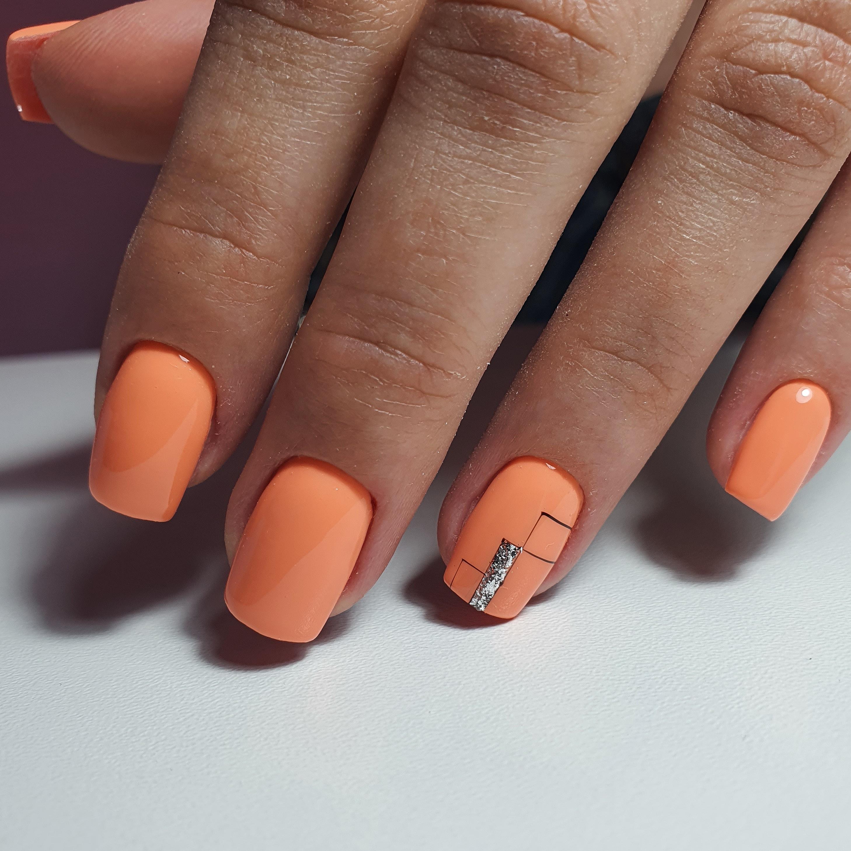 Геометрический маникюр с серебряными блестками в оранжевом цвете на короткие ногти.