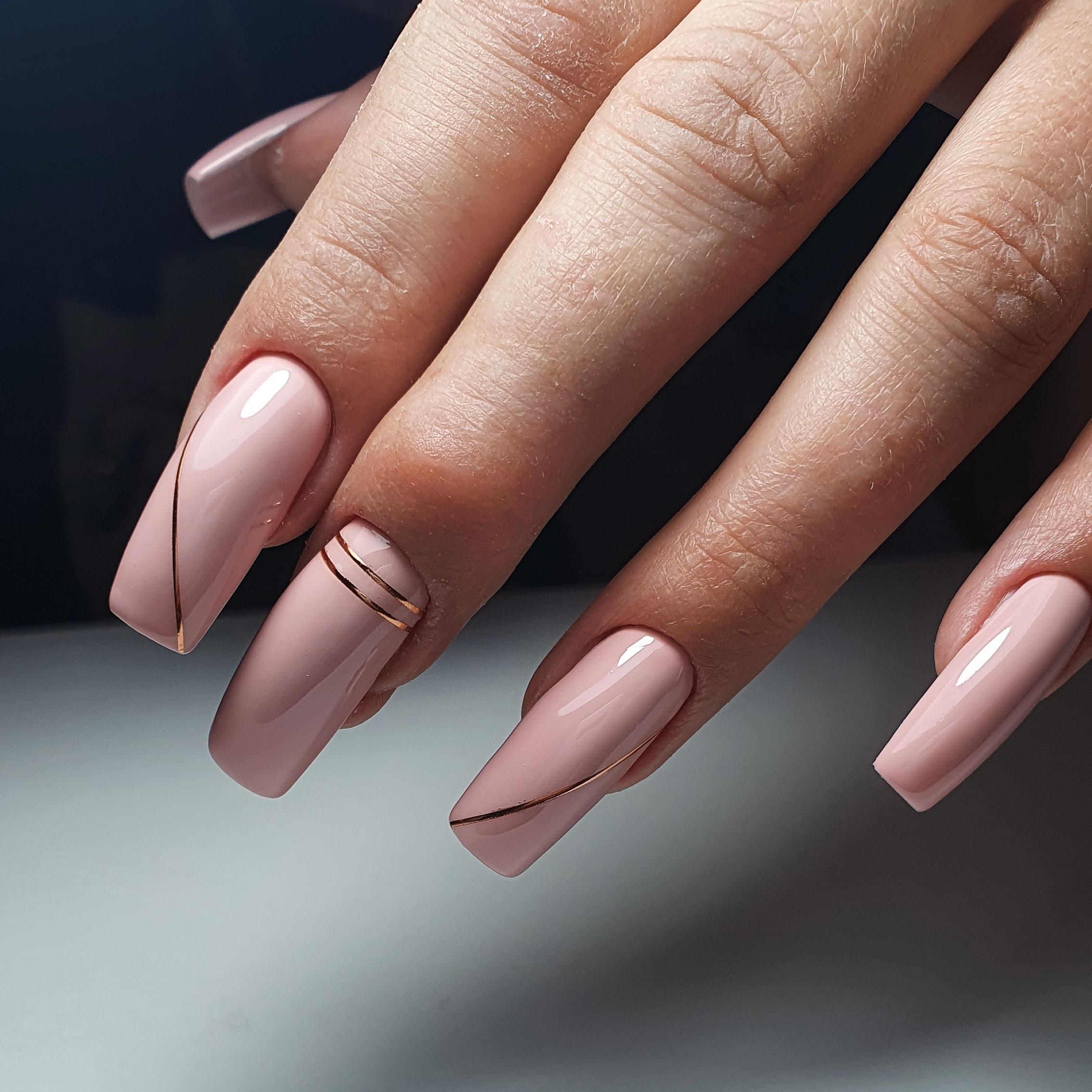 Маникюр с золотыми полосками в розовом цвете на длинные ногти.