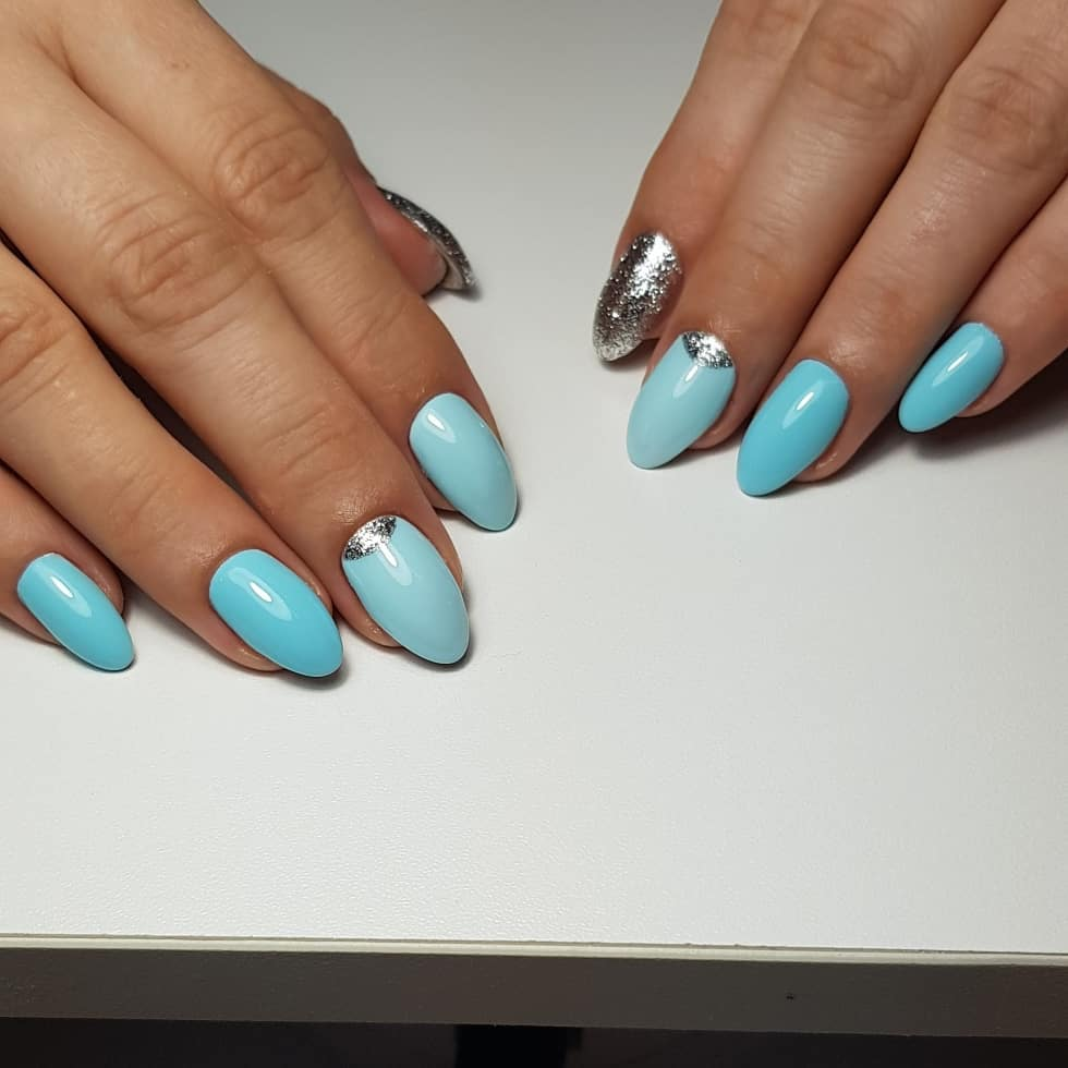 Маникюр с лунным дизайном и серебряными блестками в голубом цвете.