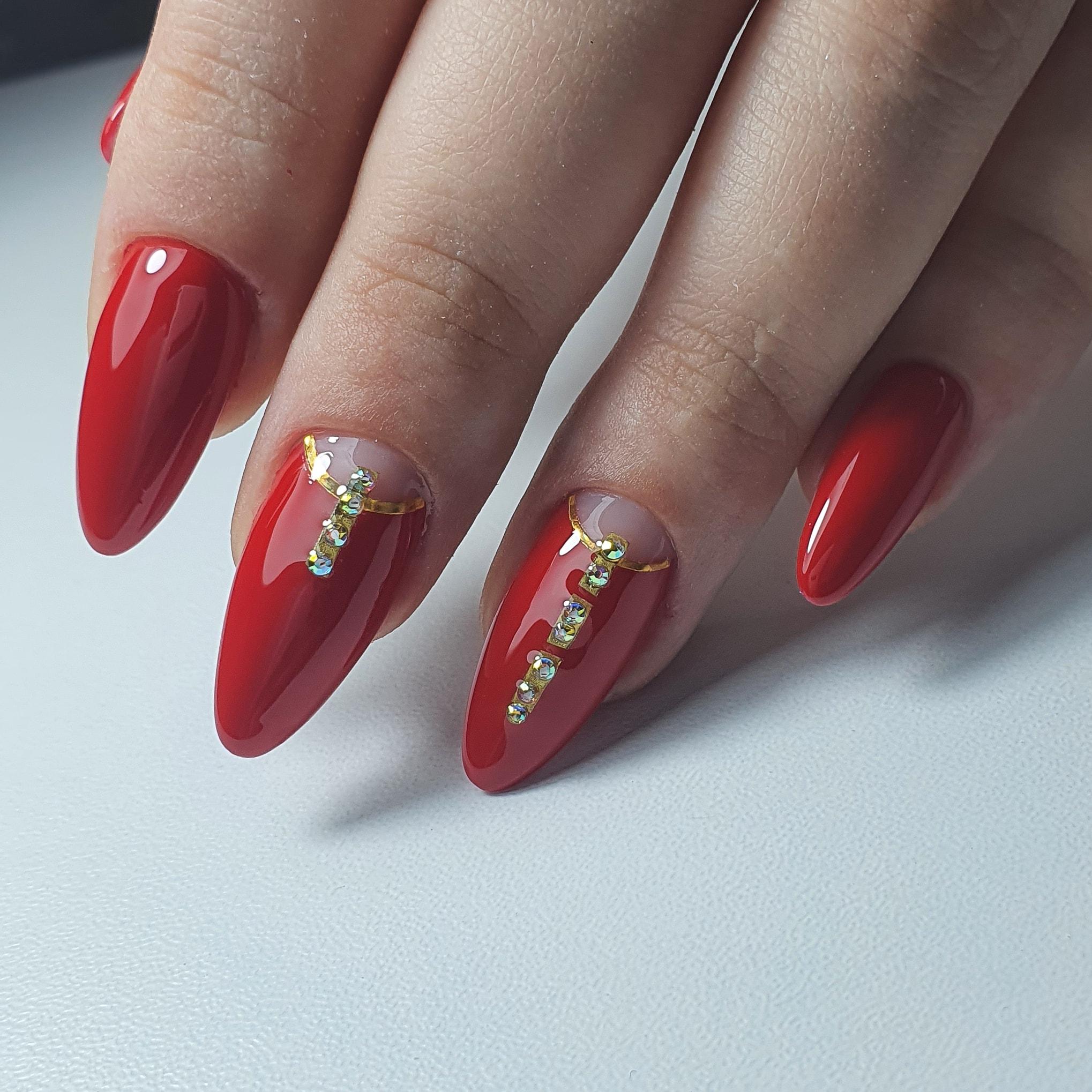 Маникюр с лунным дизайном и стразами в красном цвете на длинные ногти.
