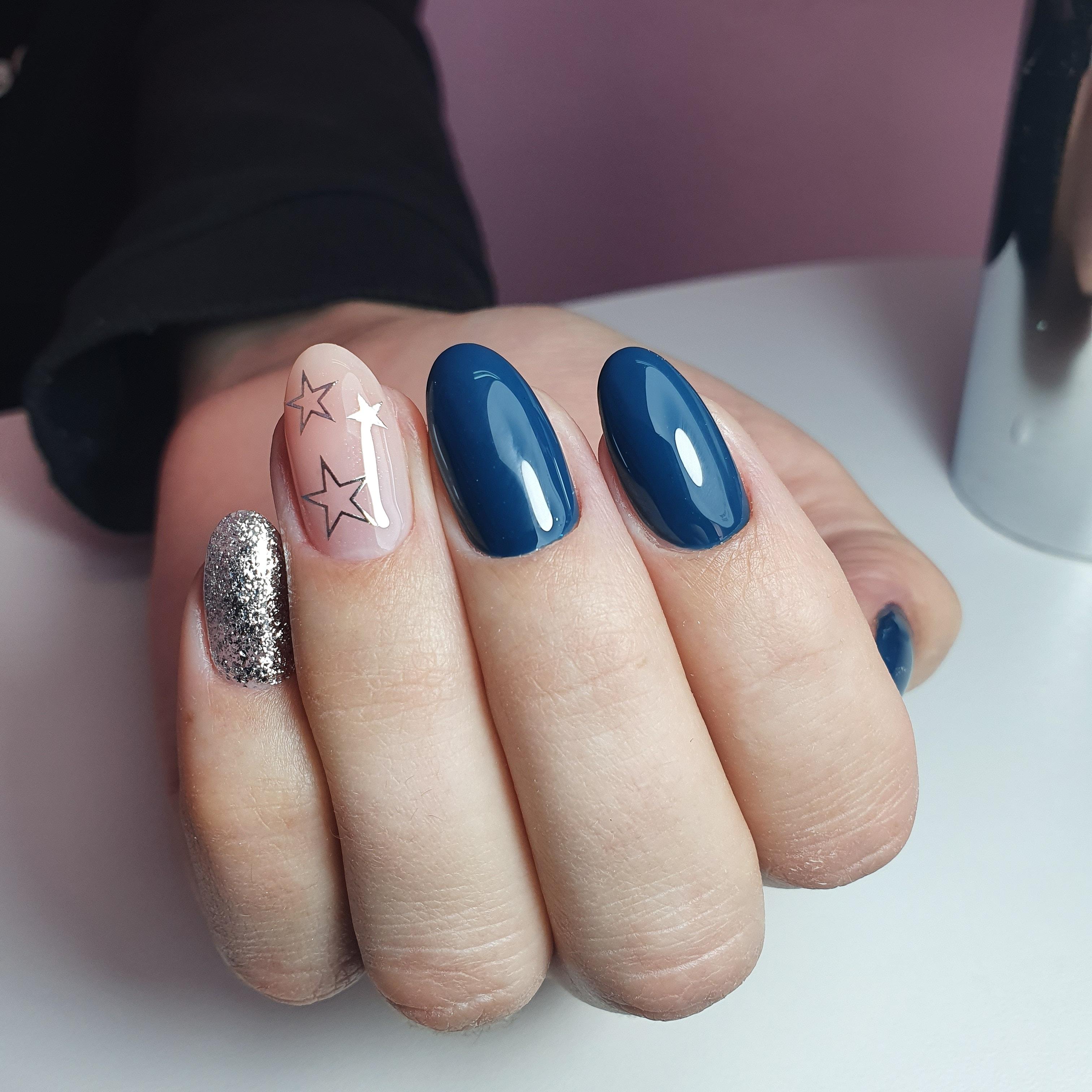 Маникюр со звездочками и серебряными блестками в темно-синем цвете.
