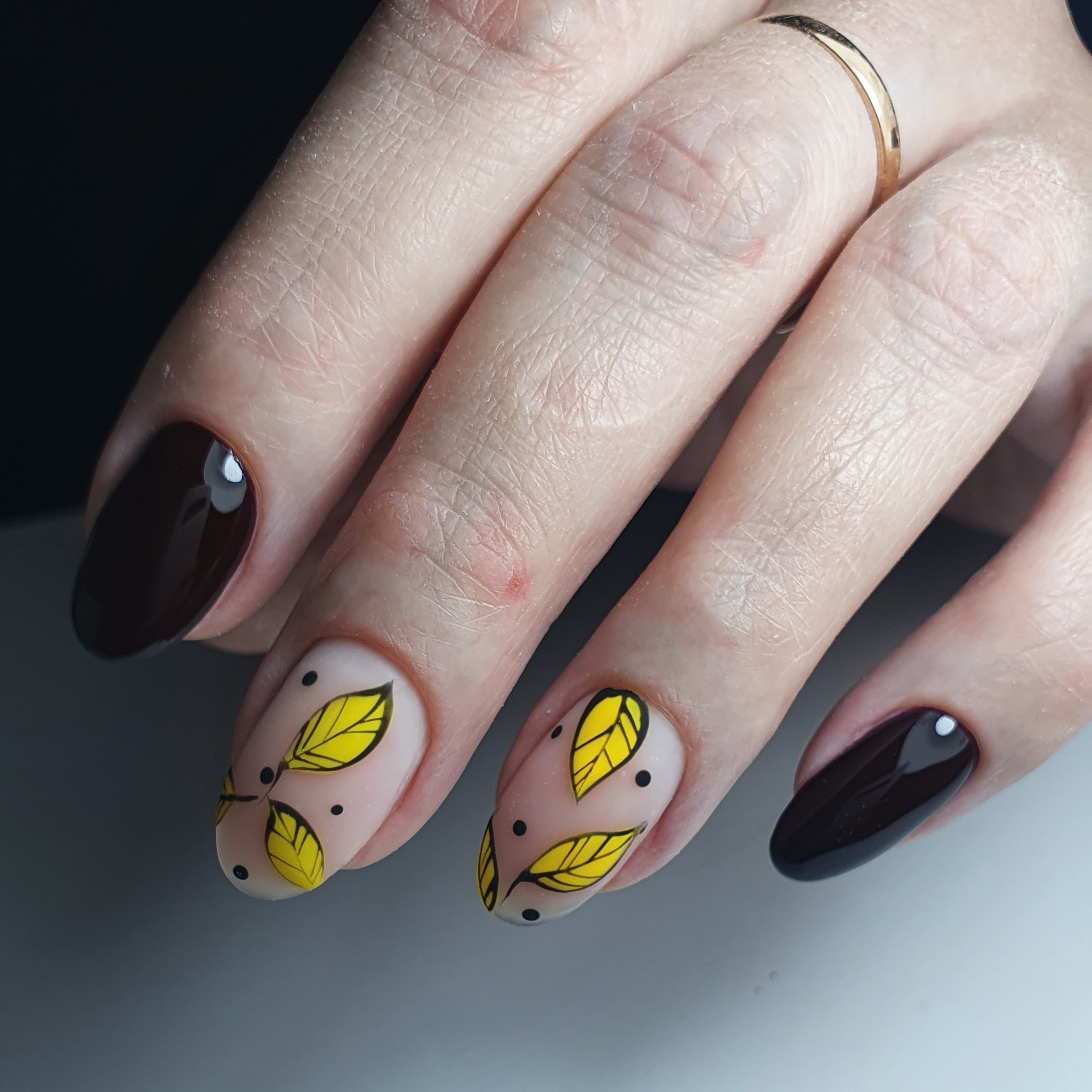 Осенний маникюр с листочками в шоколадном цвете на длинные ногти.