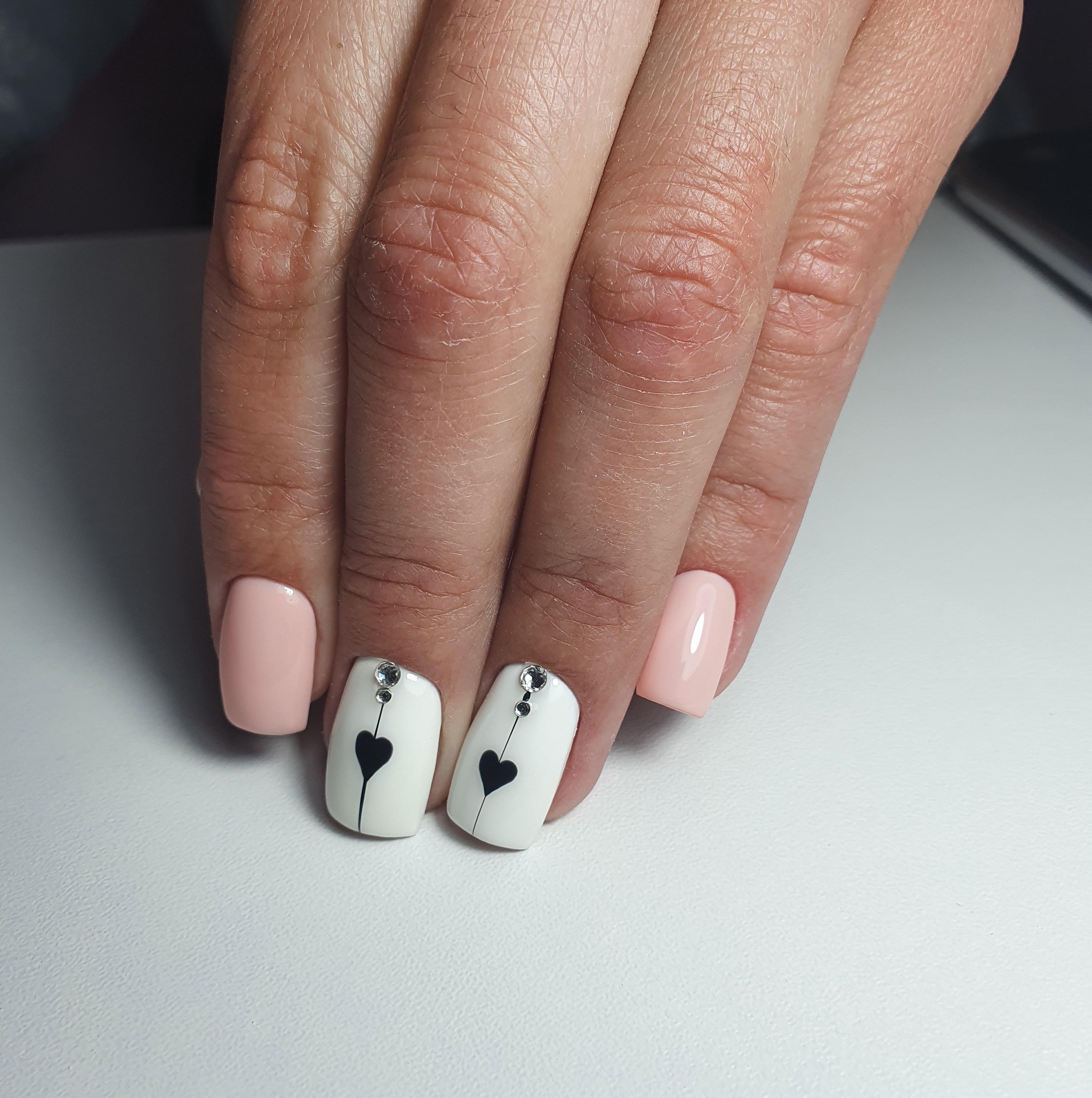 Маникюр с сердечками и стразами в персиковом цвете на короткие ногти.