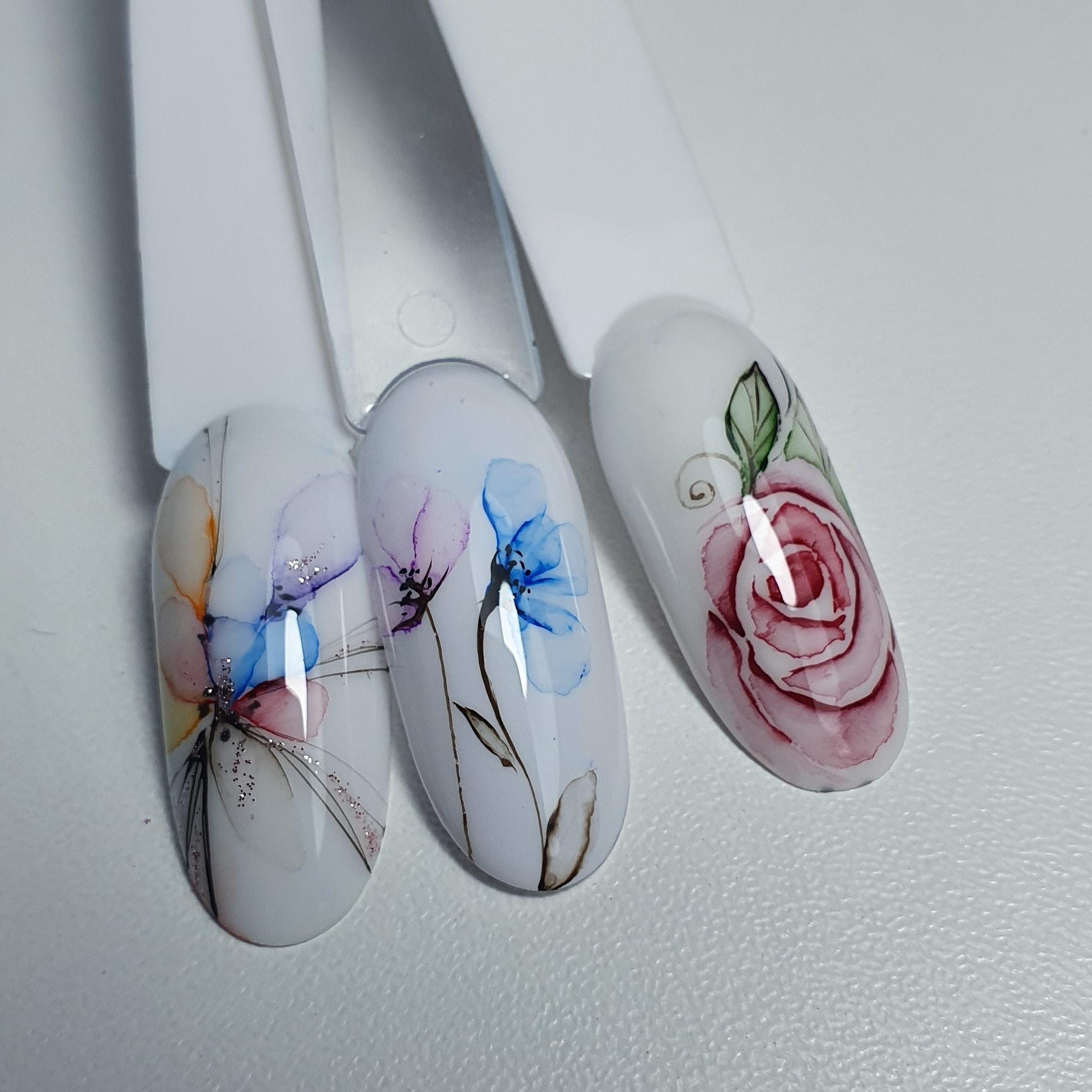 Маникюр с акварельным цветочным рисунком в белом цвете.