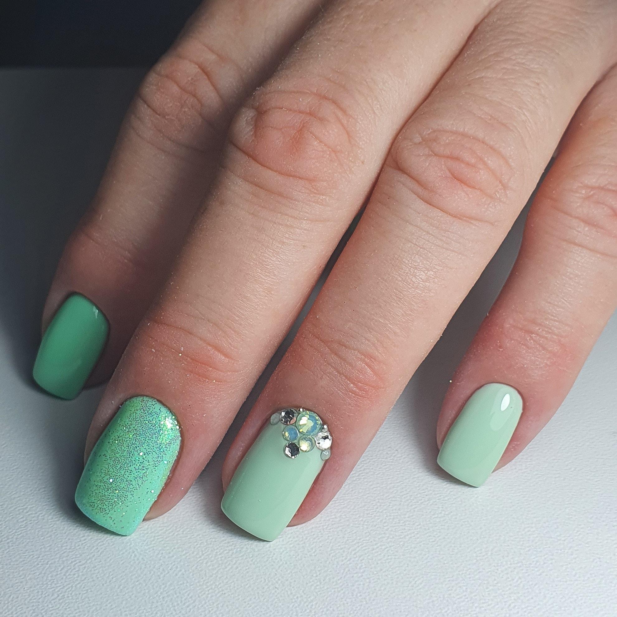 Маникюр с блестками и стразами в салатовом цвете на короткие ногти.