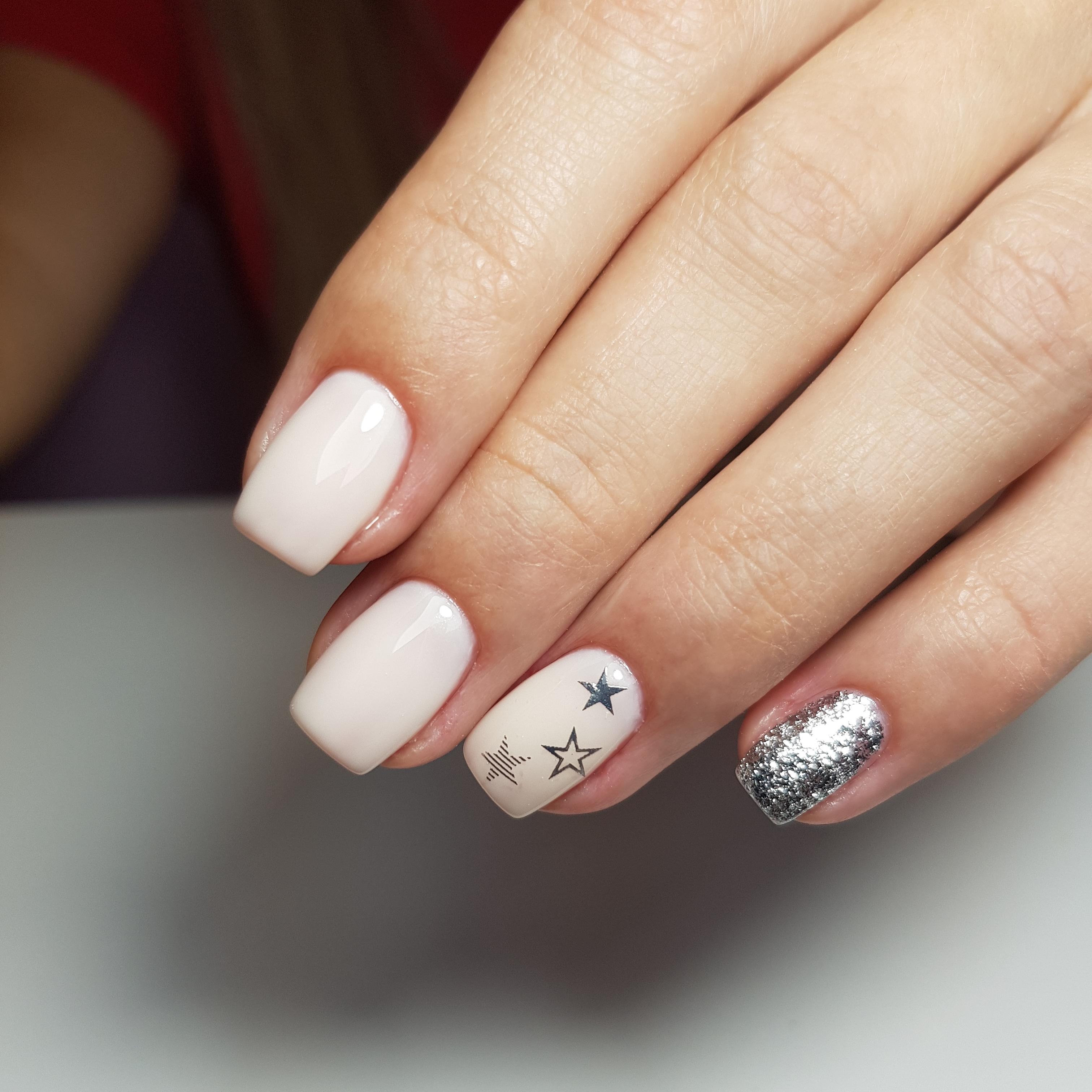 Маникюр со звездочками и серебряными блестками в молочном цвете.