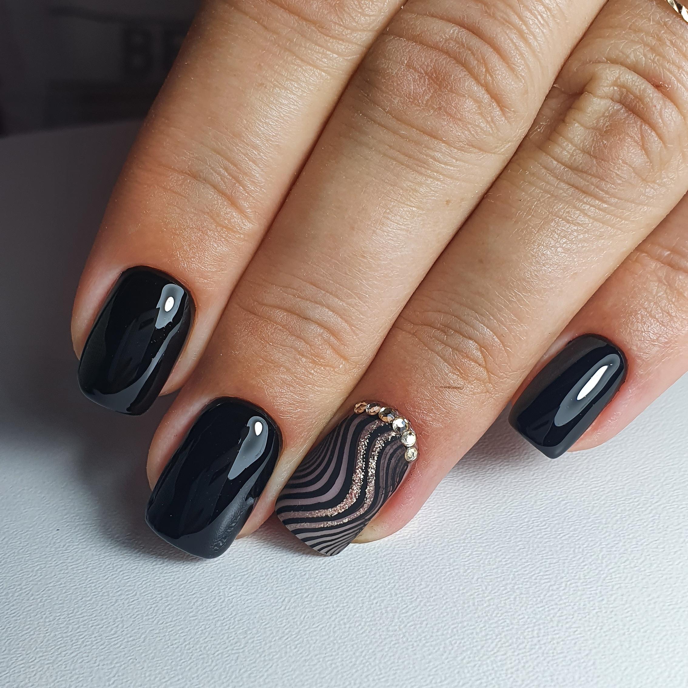 Маникюр со слайдерами, блестками и стразами в черном цвете на короткие ногти.