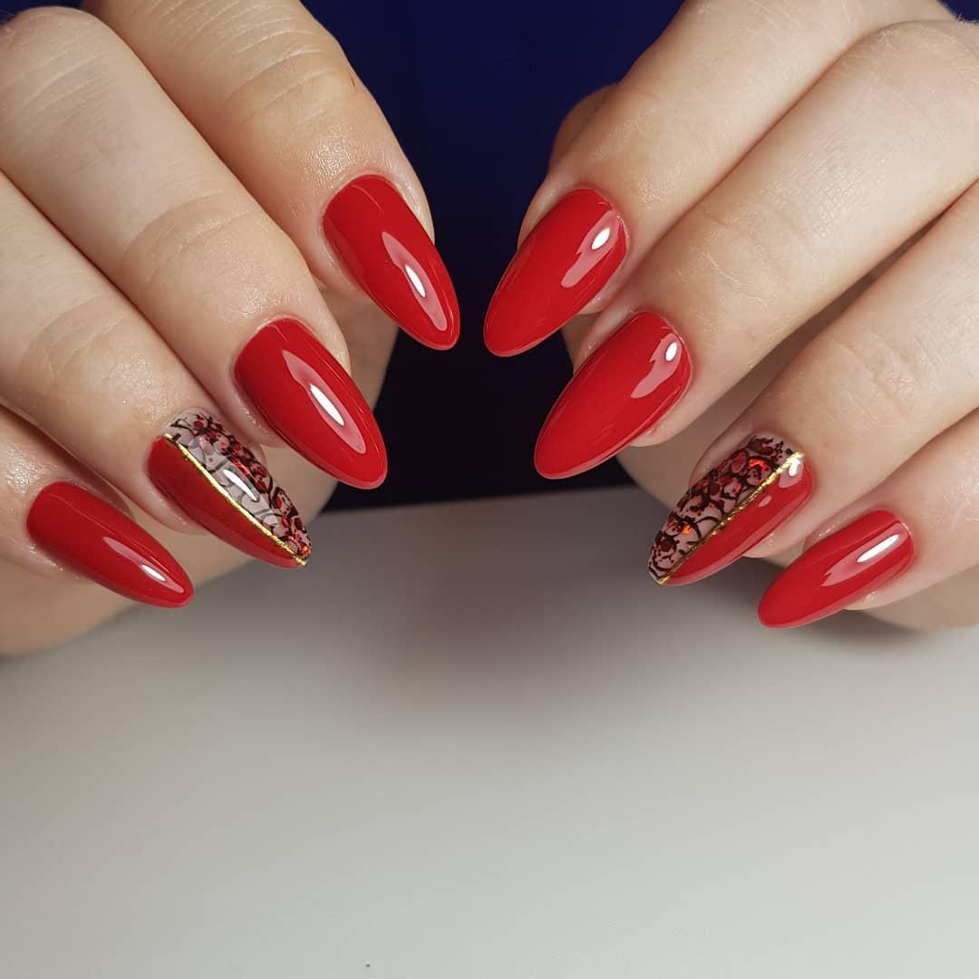 Маникюр с кружевным дизайном и золотыми полосками в красном цвете.