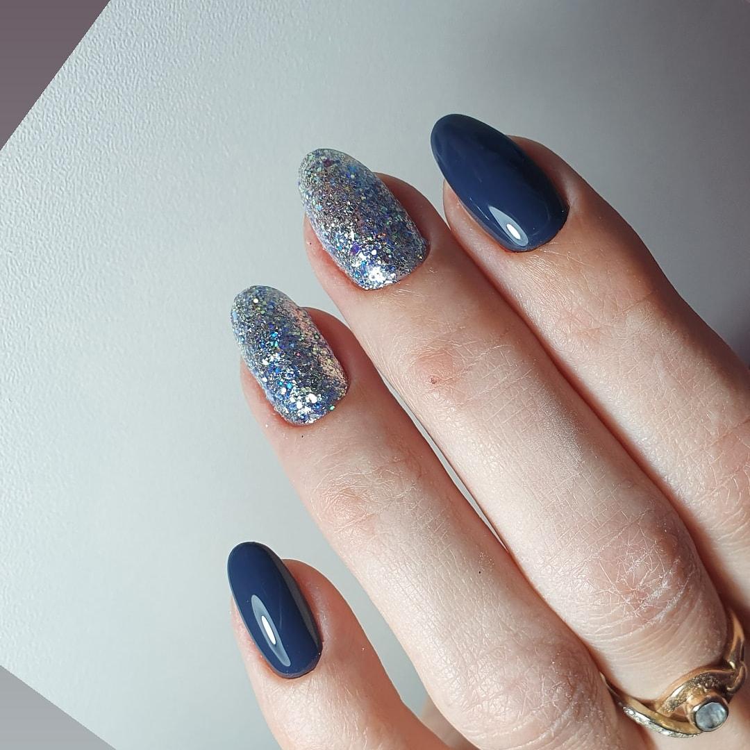 Маникюр с серебряными блестками в темно-синем цвете на длинные ногти.