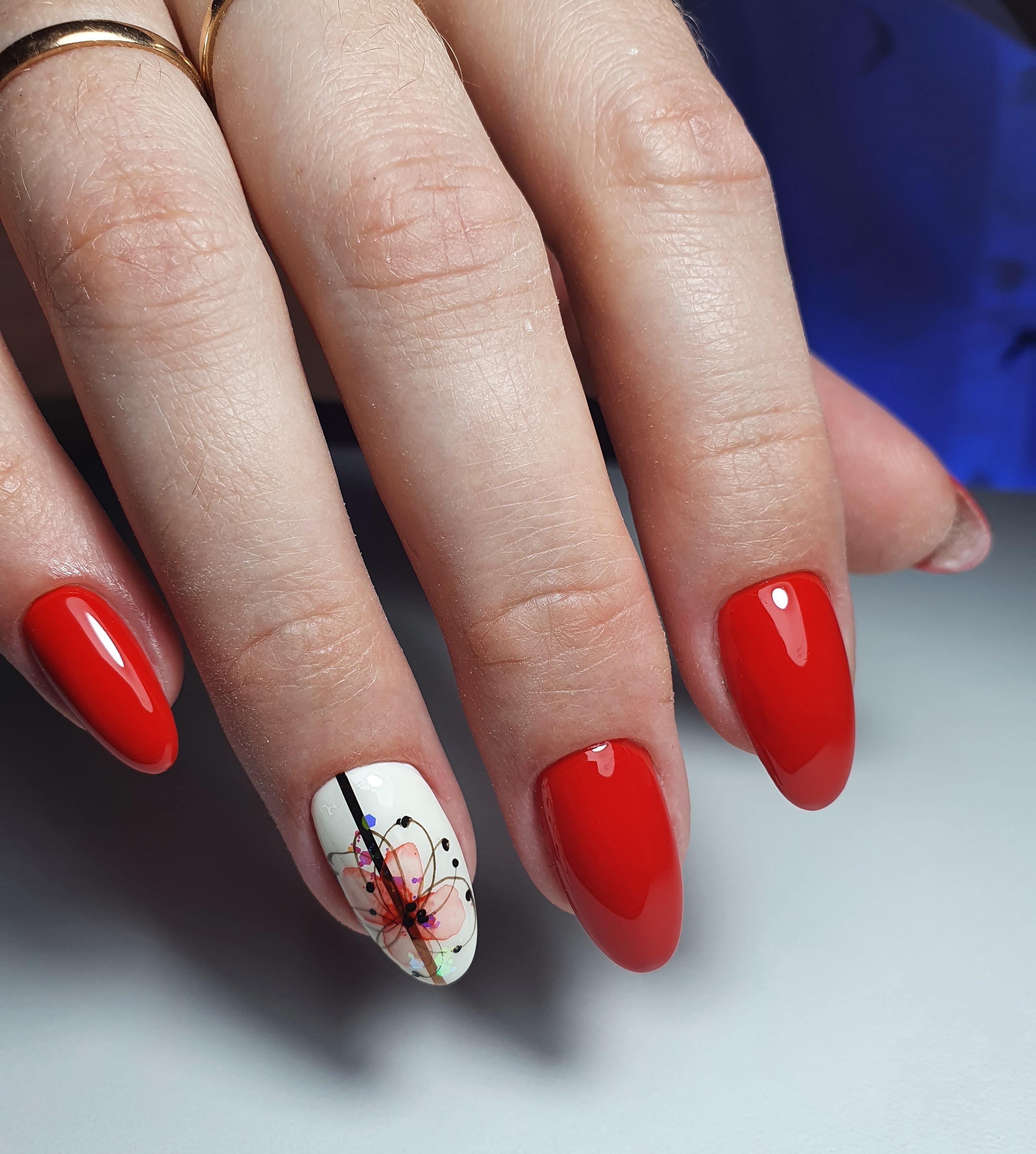 Маникюр с акварельным цветочным рисунком в красном цвете на длинные ногти.