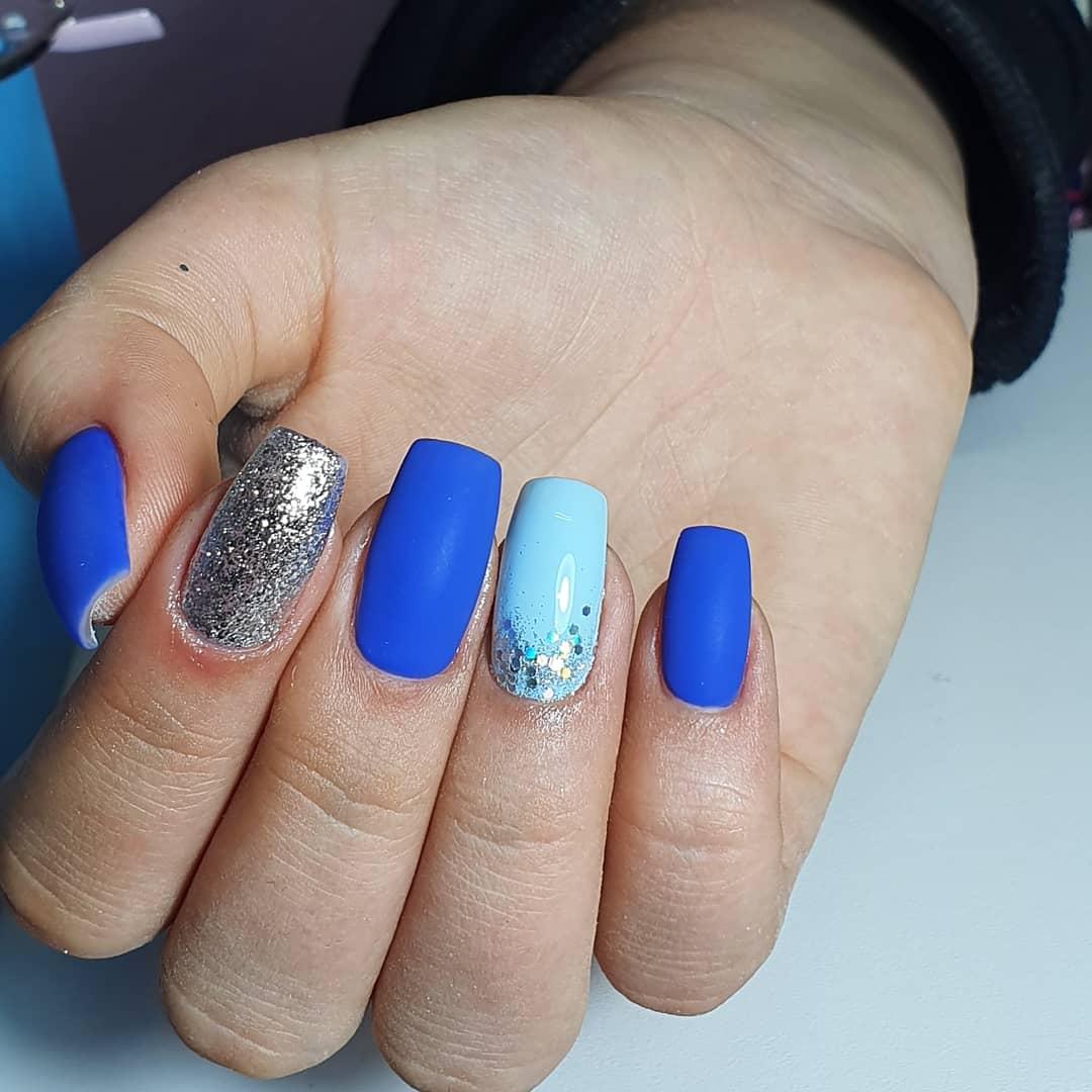 Матовый маникюр с серебряными блестками в синем цвете.