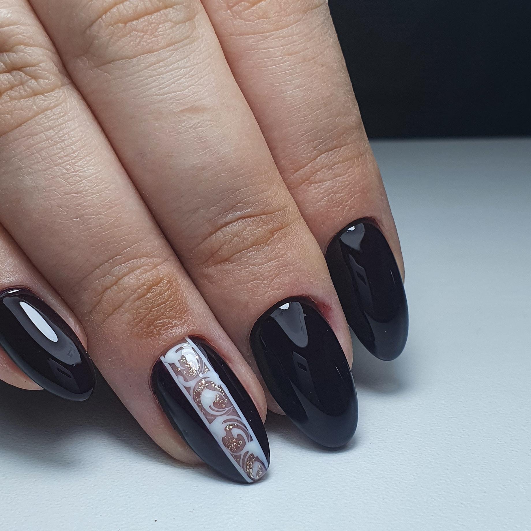 Маникюр с кружевным дизайном и блестками в черном цвете на короткие ногти.